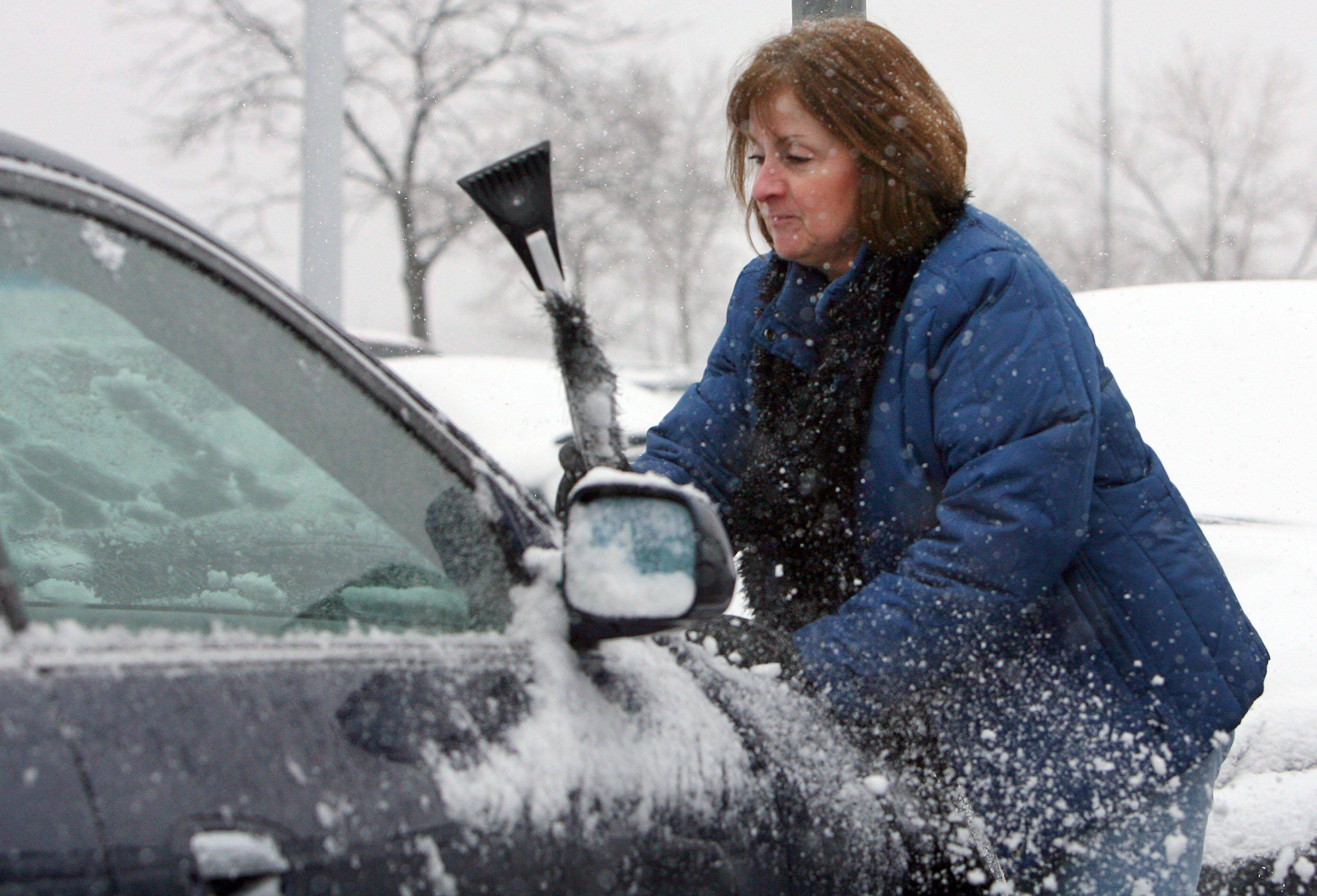Deb Bresloff of Mundelein cleans off her car at Westfield Hawthorn mall in Vernon Hills. The area got its first winter storm of the year Thursday.