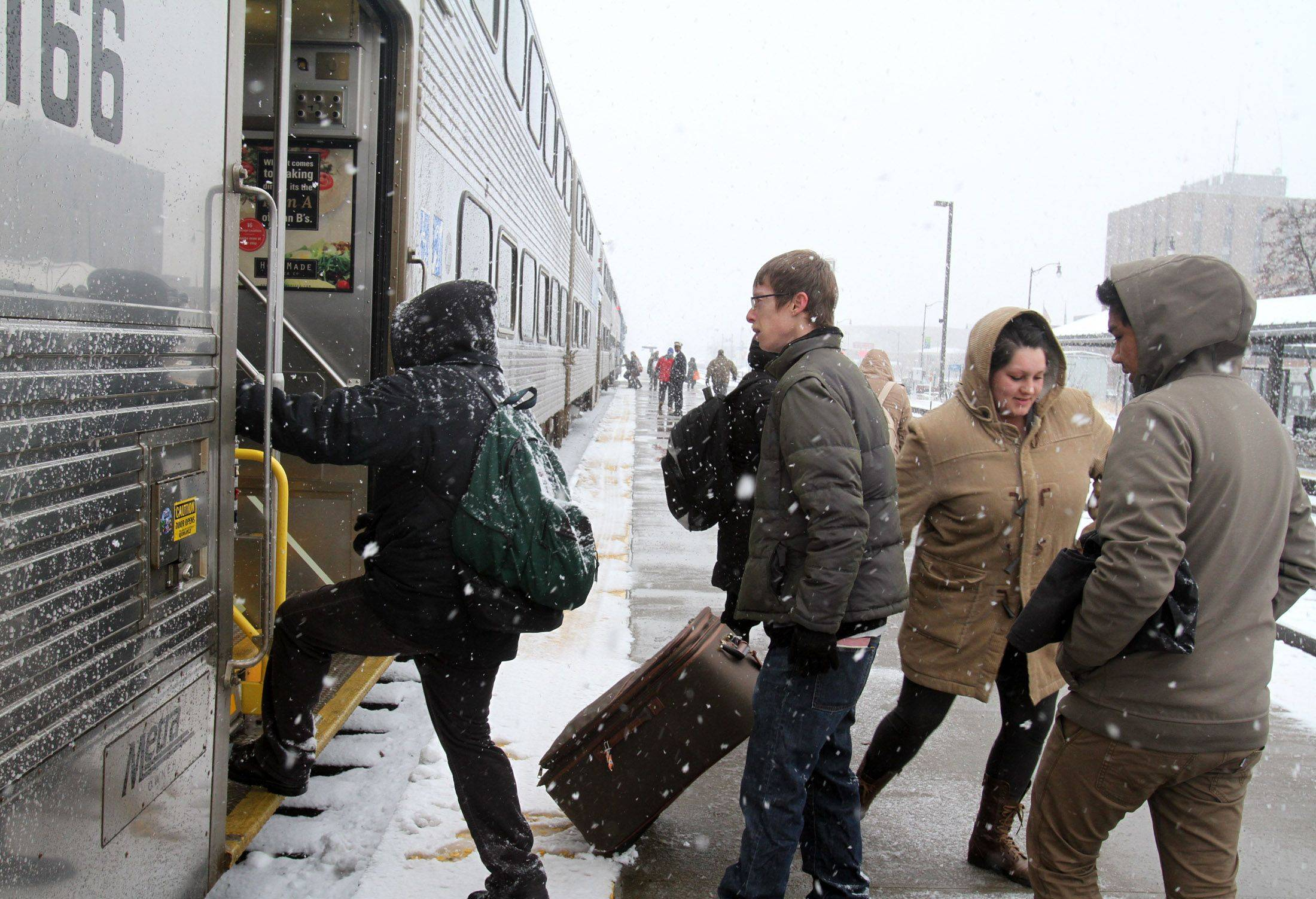 Commuters, including Adrian Jacobe of Lakemoor, far right, board the train at the Metra Station in Des Plaines.