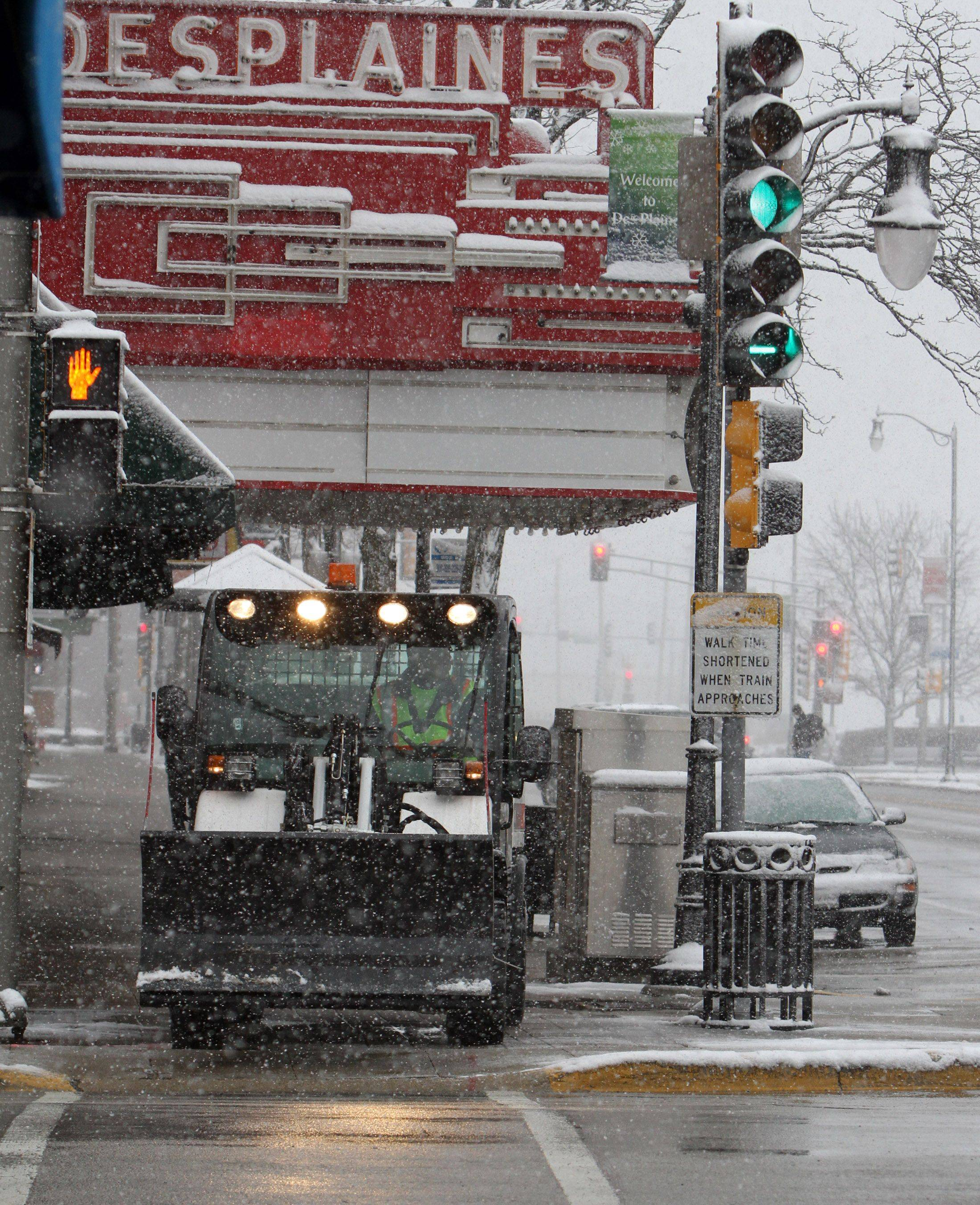 Vic Kamka with Des Plaines Public works plows the sidewalk along Northwest Highway.