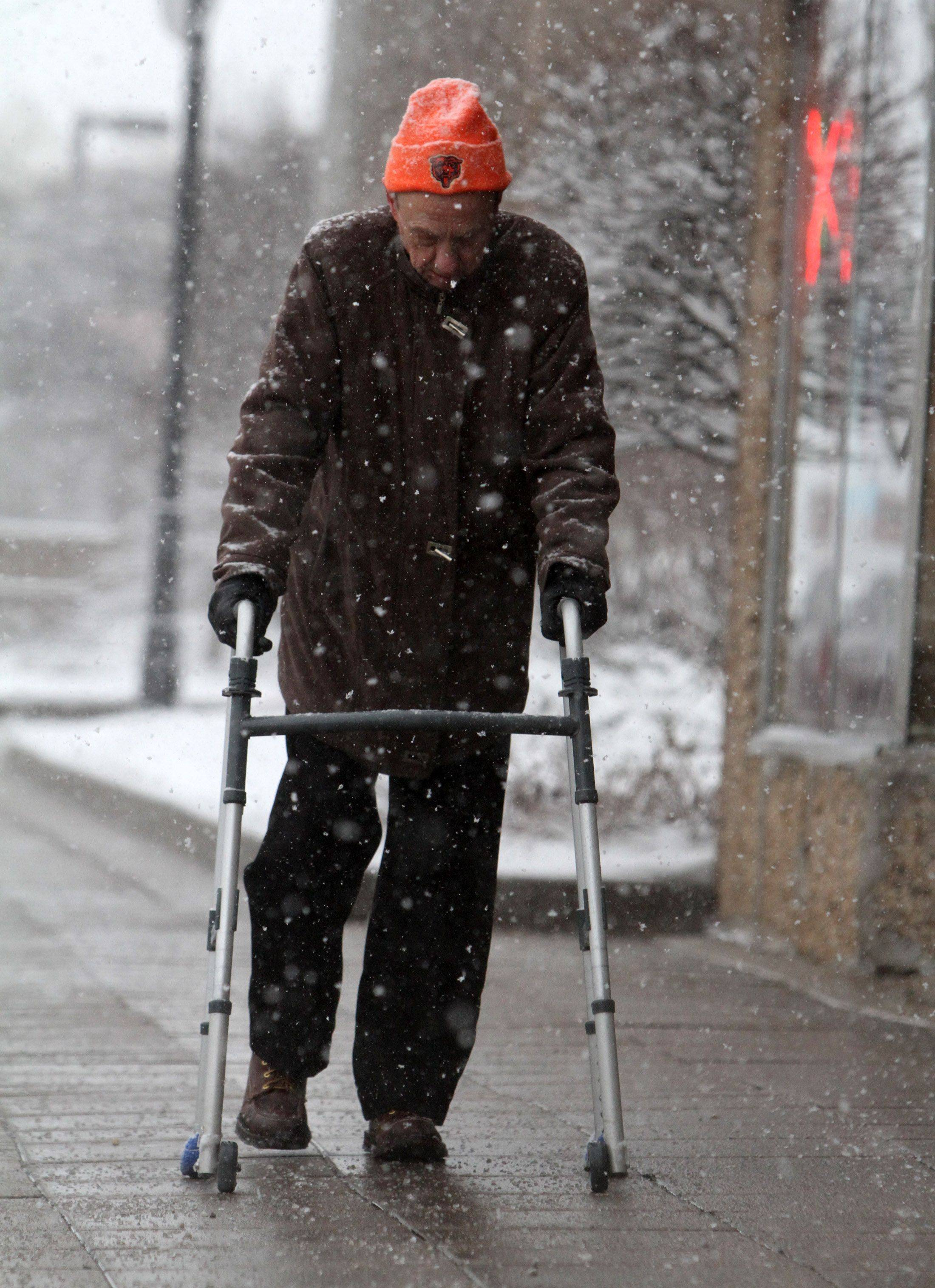 Florian Bialas walks along sidewalk on Northwest Highway as snow falls in Des Plaines. Bialas said he was headed for a warm dinner and coffee nearby.