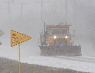 A plow already scraping accumulating snow off the roadway leads a pack of cars as they head eastbound on Route 38 in Elburn on Thursday morning after 9AM, January 12.
