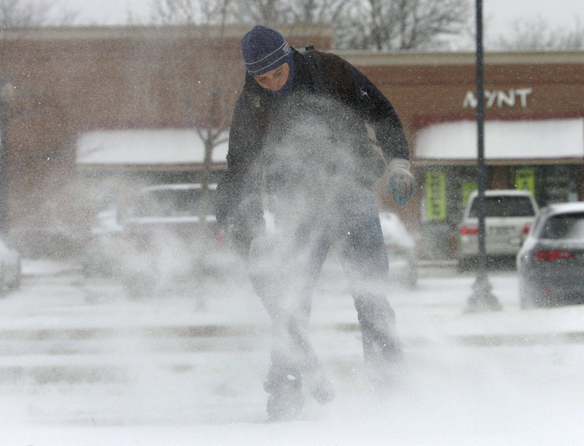 Damian Lopez of Streamwood finally gets the snowfall he's been waiting for all season for his landscaping business. He uses a leaf blower to clear a path in front of Oberweis in the Town Square in Schaumburg.