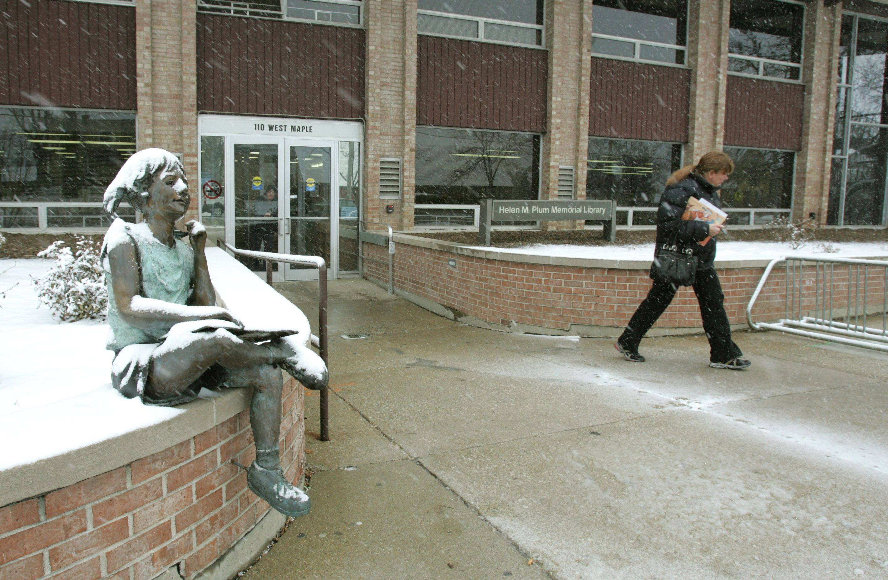 Snow coats a statue outside the Helen Plum Memorial Library in Lombard during Thursday's storm.