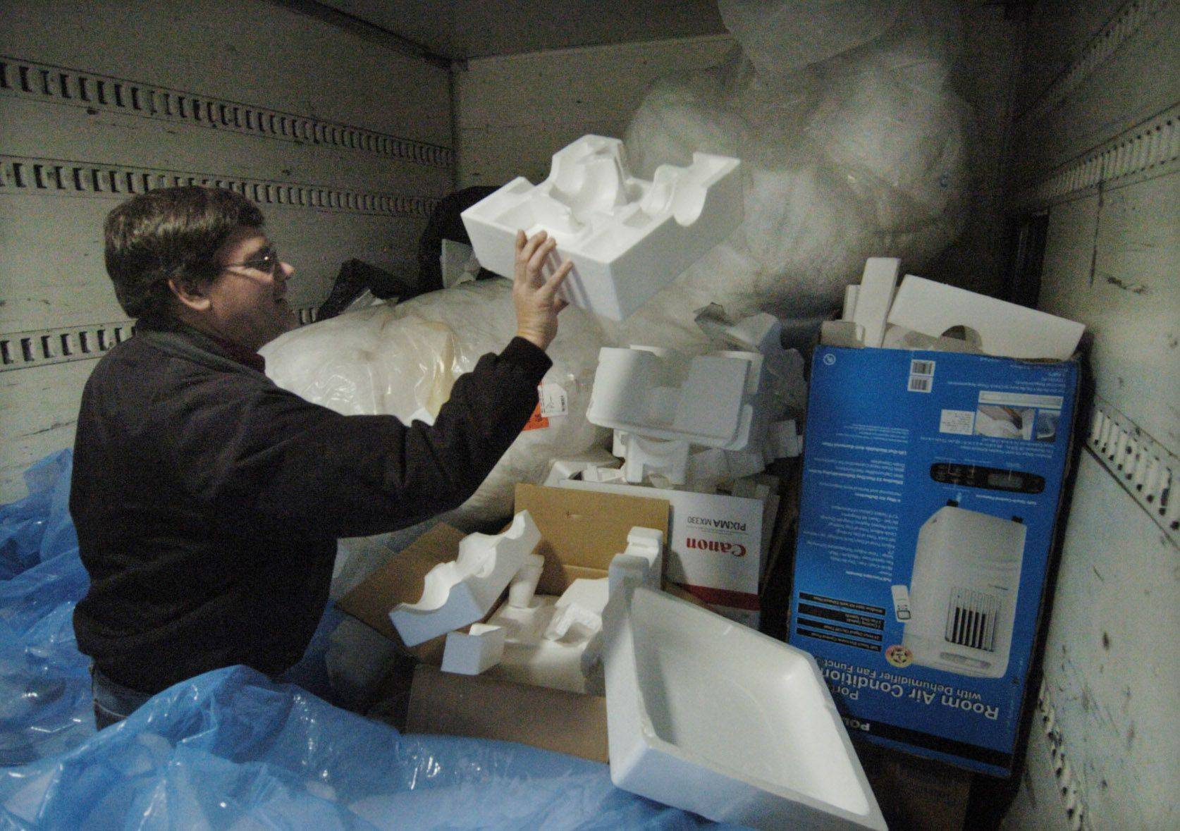 Ken Santowski, owner of Chicago Logistic Service in Elgin, goes through a pile of foam products Friday. His business serves as a drop-off facility, and Santowski also does pickups in Algonquin, Elgin and Lakewood.