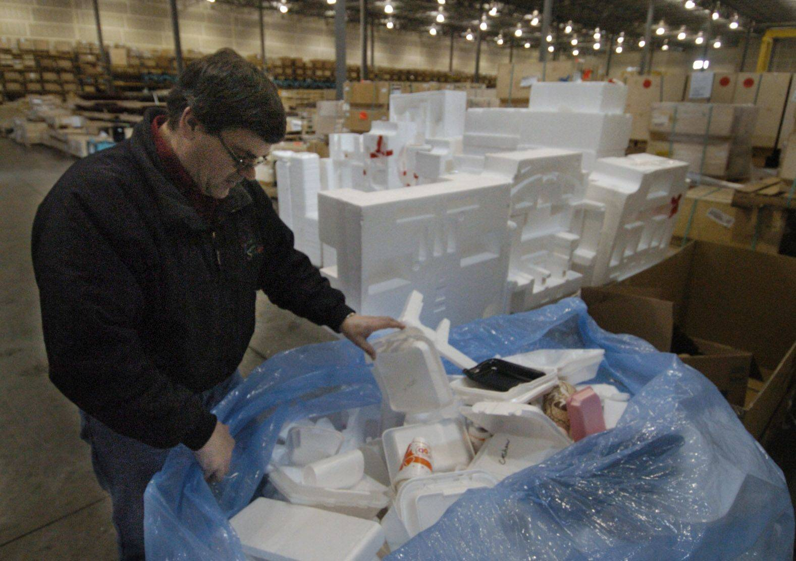 Ken Santowski, owner of Chicago Logistic Service in Elgin, goes through a bag of packing foam and foam lunch trays, which he will take to a recycling facility in North Aurora.