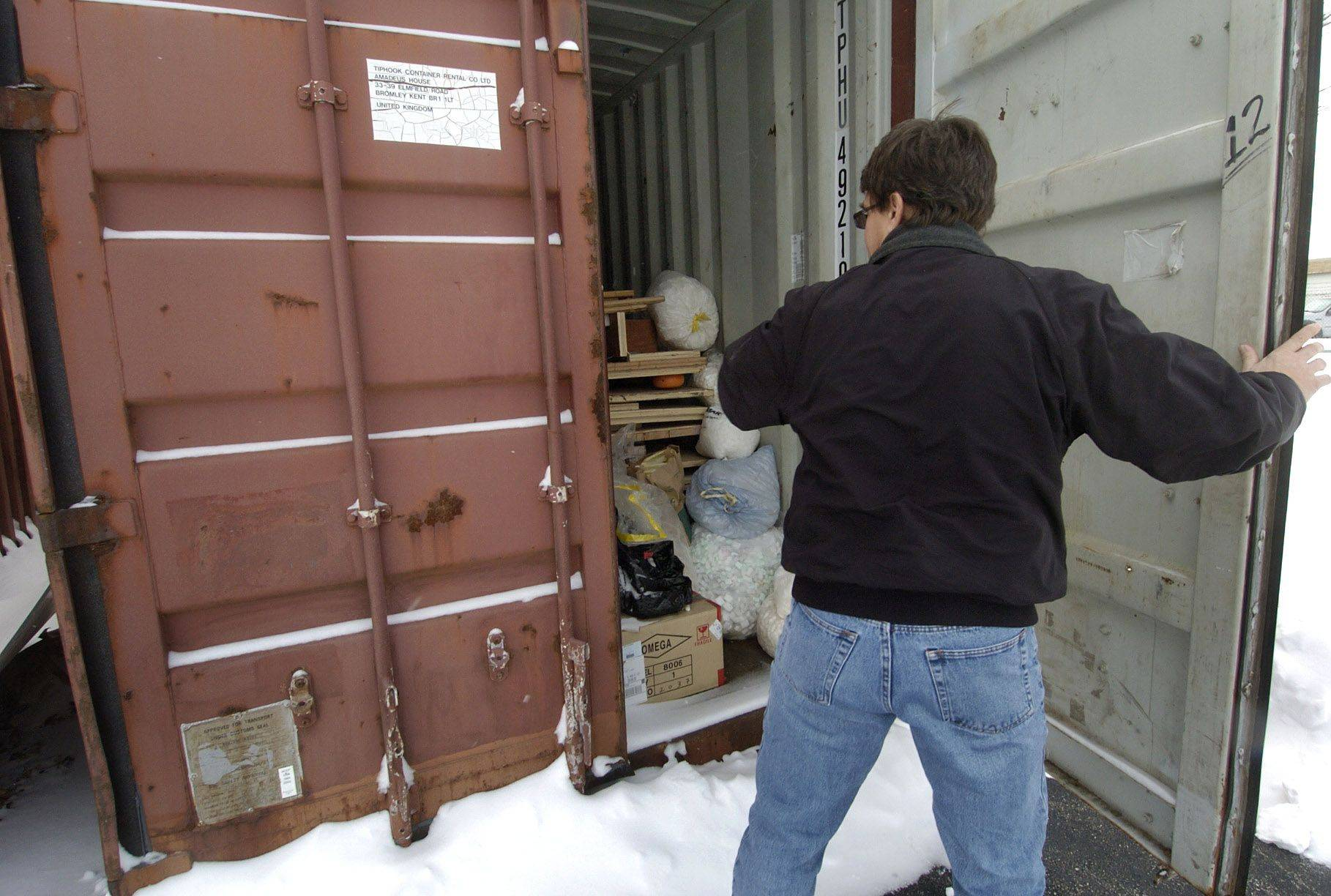 Ken Santowski opens a storage container where he keeps bags of foam peanuts that people dropped off for recycling.