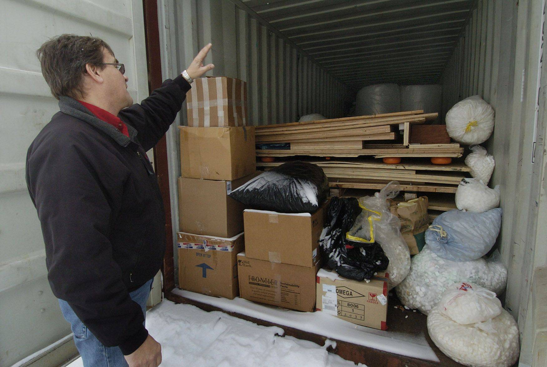 Ken Santowski looks inside a storage container where he keeps bags of foam peanuts that people dropped off for recycling.