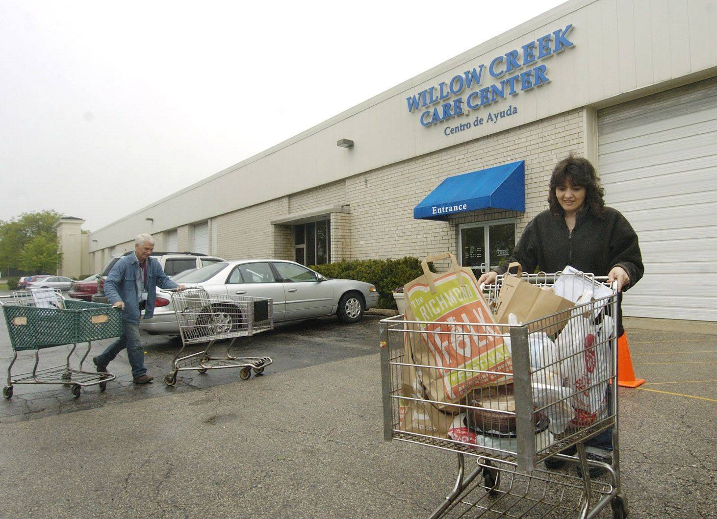Volunteer Maribel Castaneda of Lake Zurich wheels out food for a client at the Willow Creek Care Center food pantry in Hoffman Estates in May 2010. The church is seeking permission to build a new Care Center on its main campus in South Barrington.