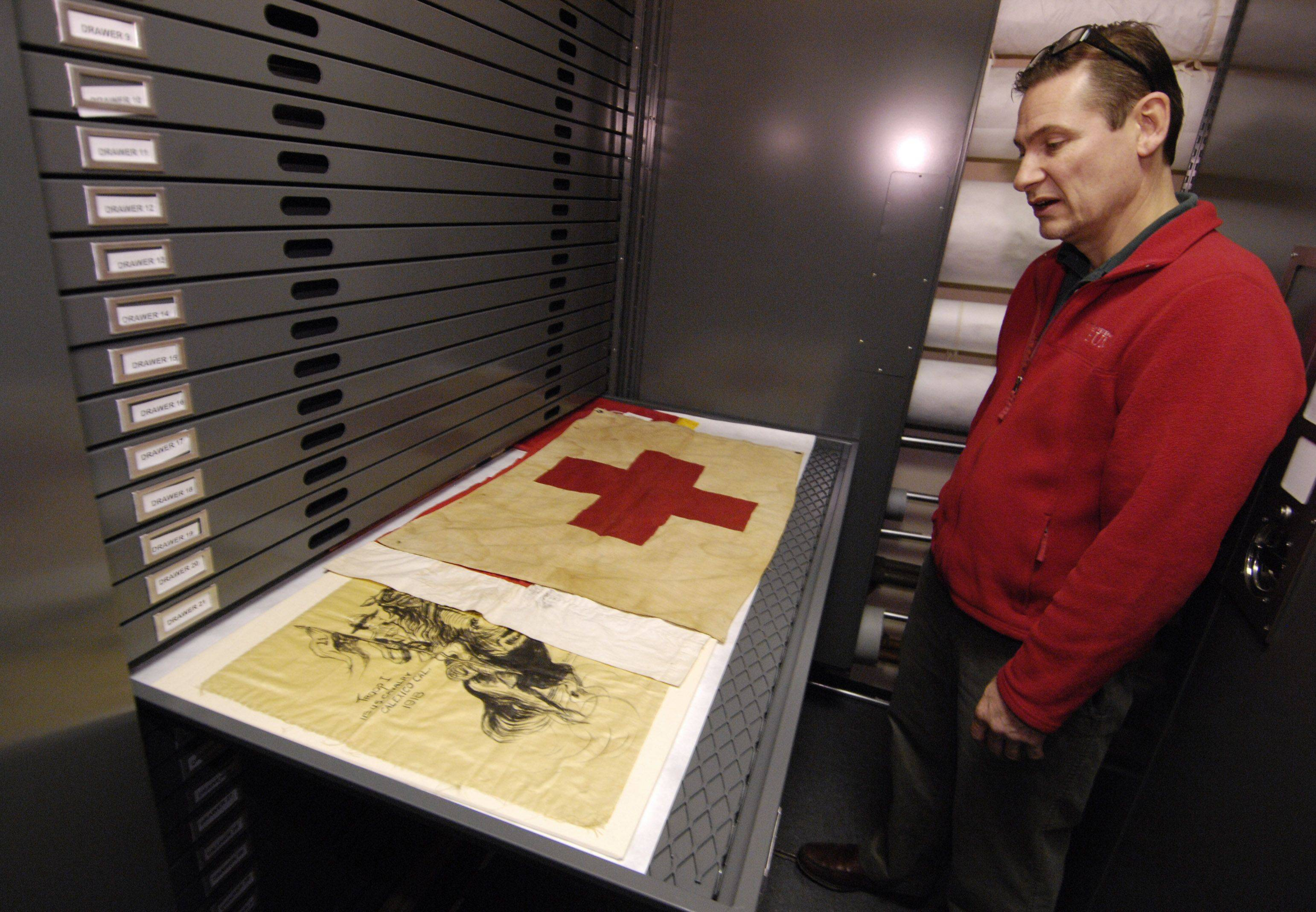 William Brewster, Curator of Collections shows off some of the flags in the archives of 1st Division Museum at Cantigny Park in Wheaton.
