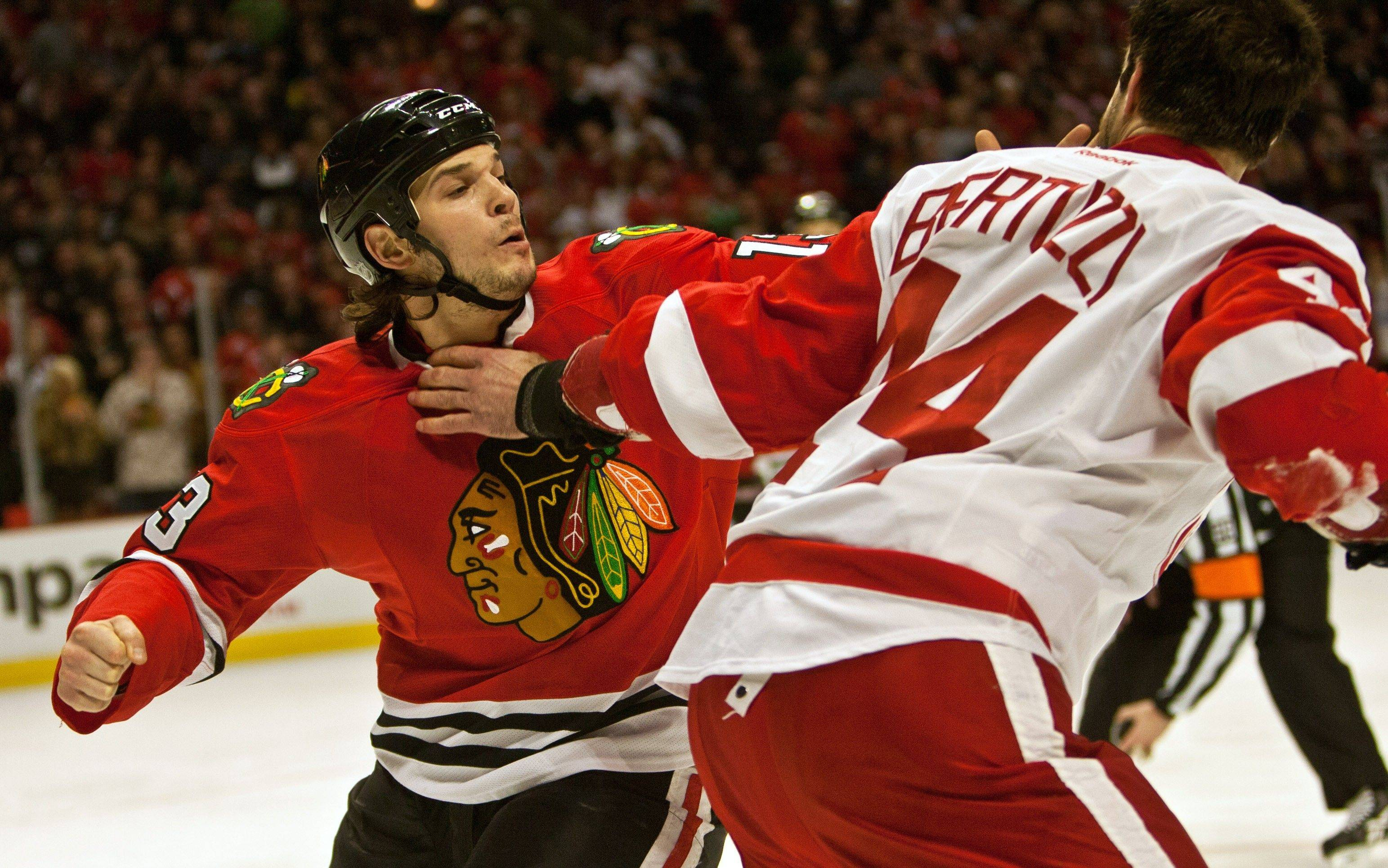 Daniel Carcillo, here fighting Detroit's Todd Bertuzzi on Dec. 30, 2011, will miss the rest of the season. He needs reconstructive surgery on his left knee.