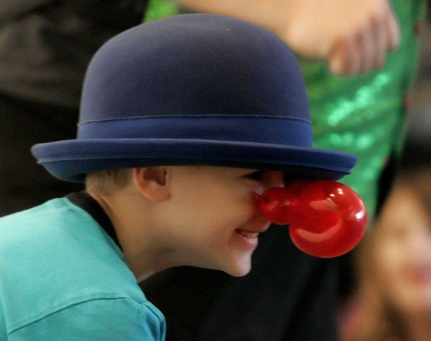 "Peter Zatek, 6, wears a balloon nose made by ""the Flying Fool"" Ken Schultz as he entertained children and adults with stunts, juggling, and balloon animals at the Wauconda Area Library."