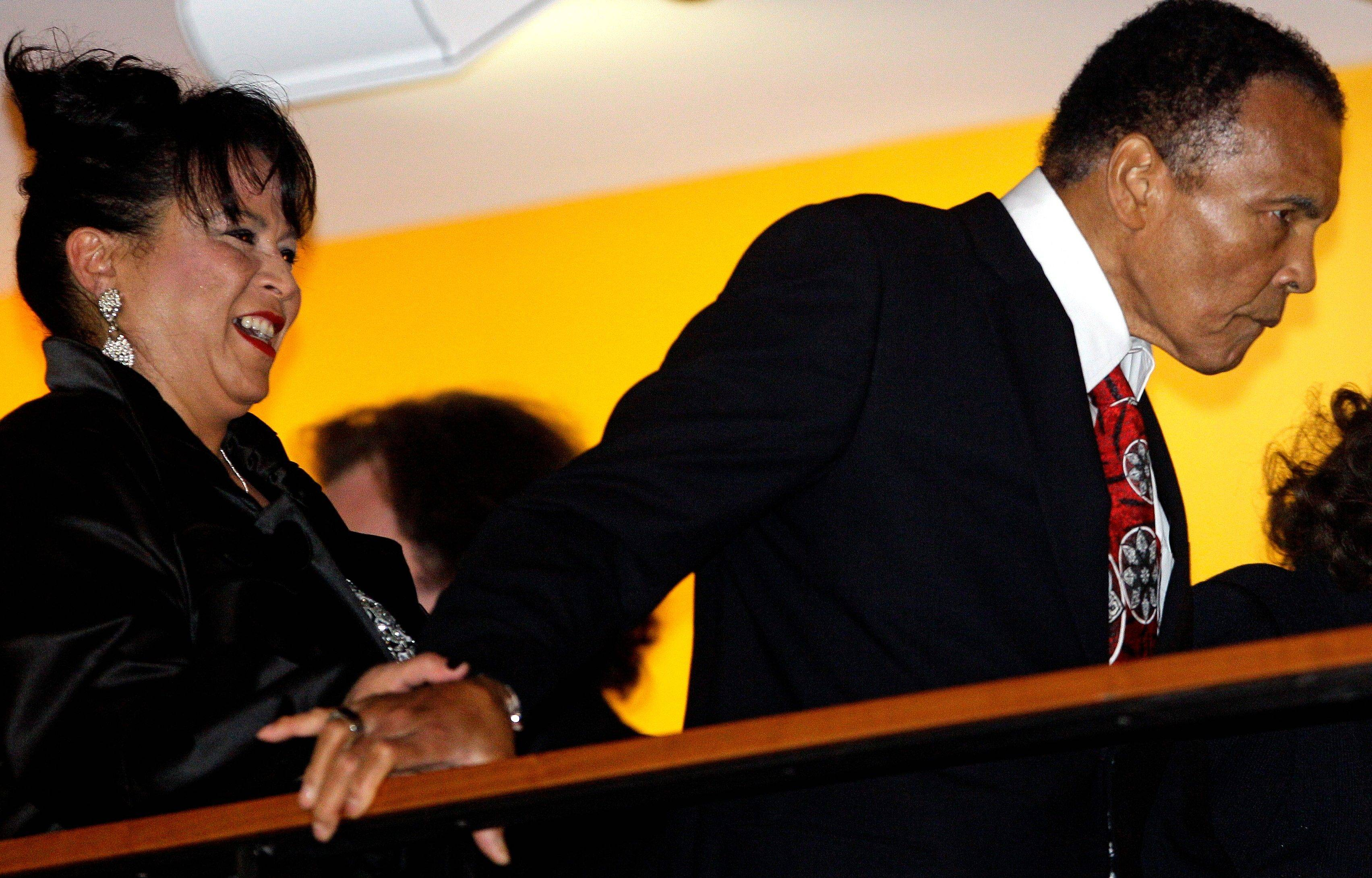 Boxing great Muhammad Ali, with the help of his sister-in-law, Marilyn Williams, makes an appearance Saturday at a balcony before the celebration for his 70th birthday at the Muhammad Ali Center.