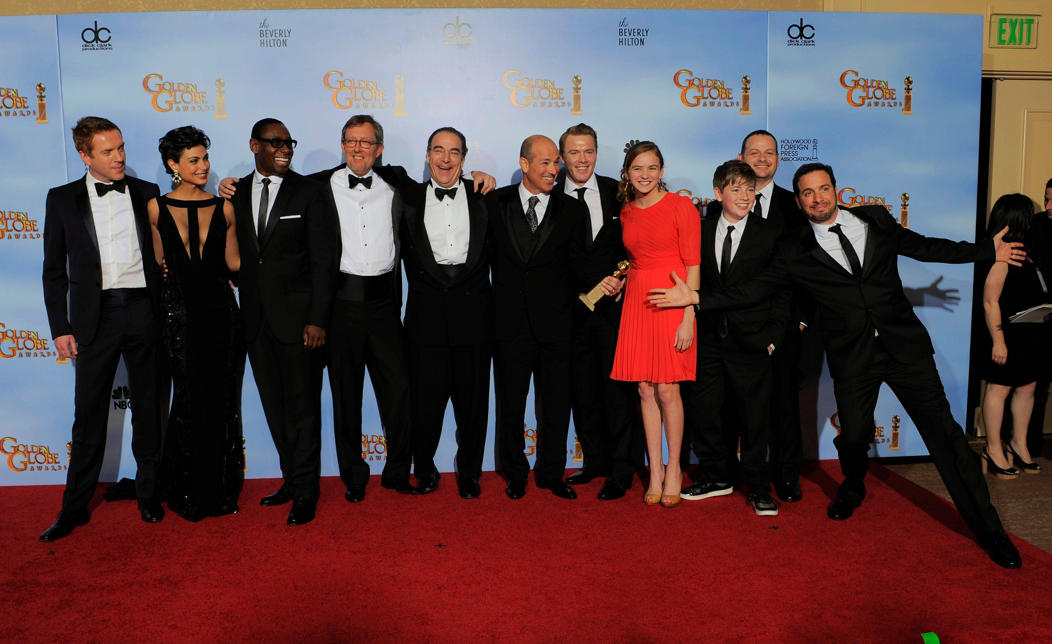 "Howard Gordan, sixth from left, and the cast and crew of ""Homeland"" pose backstage with the award for Best Dramatic Television Series during the 69th Annual Golden Globe Awards."