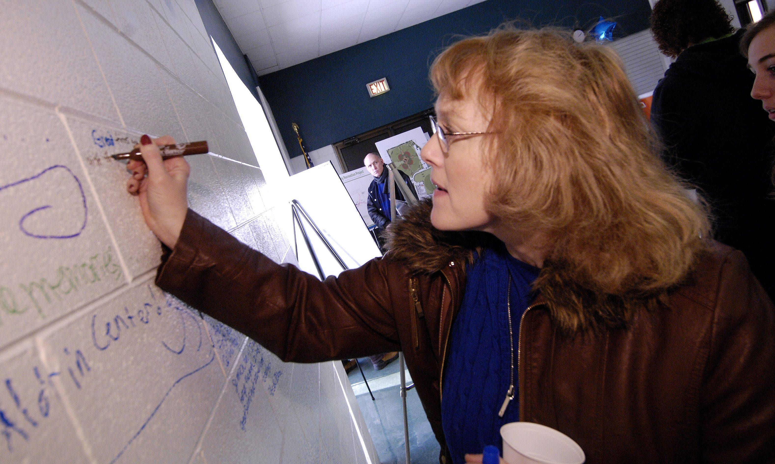 "Carol Stream resident Carol Floren, signs the wall of the Aldrin Community Center at Armstrong Park during a ""thanks for the memories"" event on Sunday. The building will be demolished in early 2012 as part of a DuPage County stormwater management project in the park."