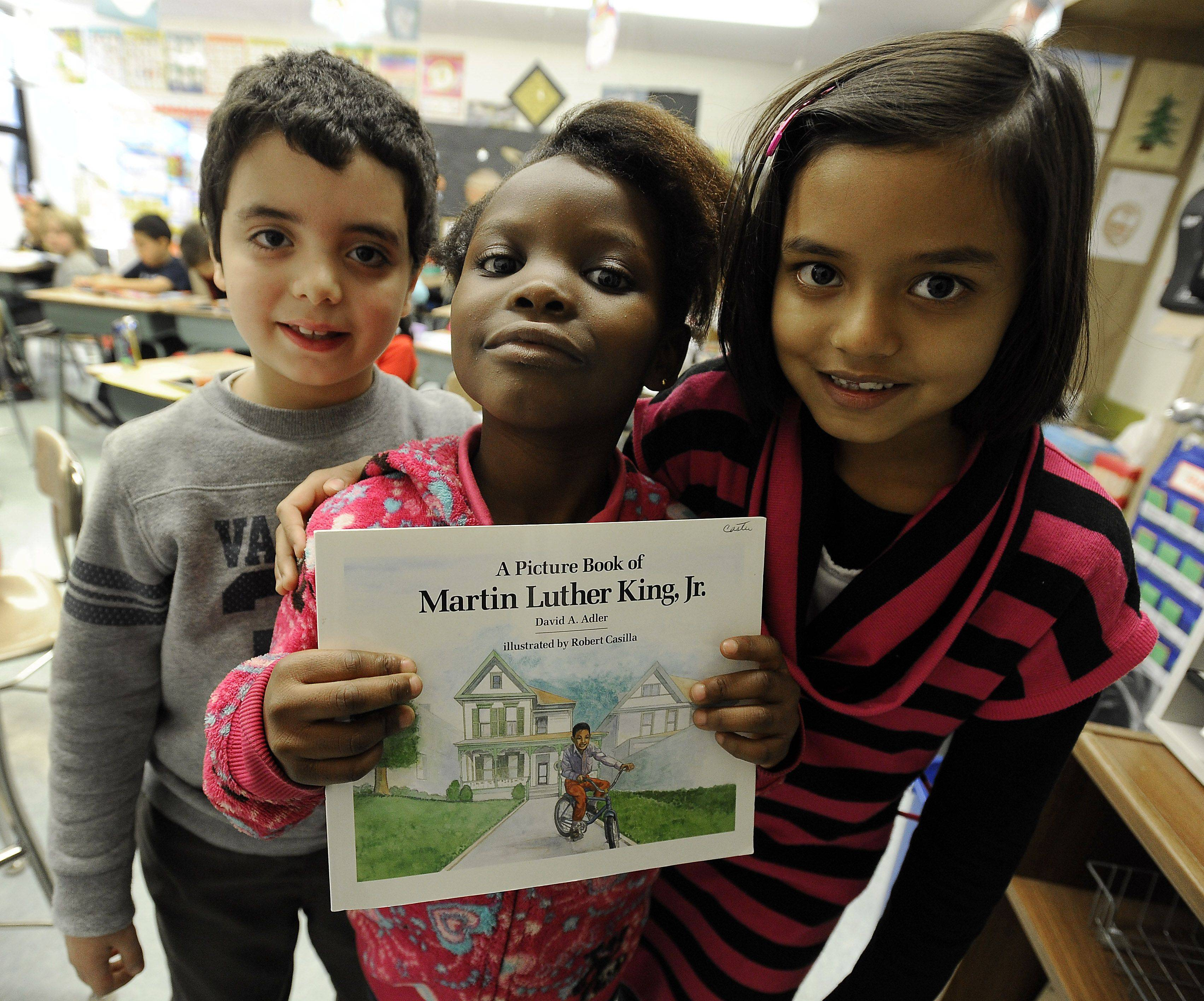 Aram Hanna,6, Shakinah Phiri,6, and Pravika Srivastava,7, of Mrs. Ann Caster 1st grade class come together to celebrate the life of Martin Luther King in their classroom at Robert Frost Elementary School in Mt. Prospect with pictures and their own thoughts written in essays.