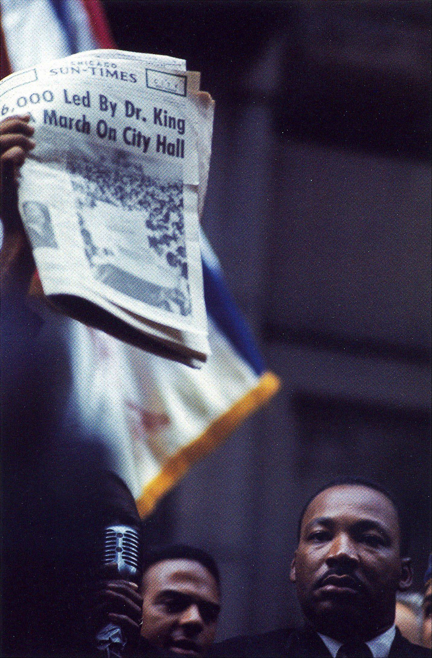 An obscured speaker holds up a newspaper, objecting to the low estimate of march numbers reported by the press, while Martin Luther King stands nearby in this undated photo.