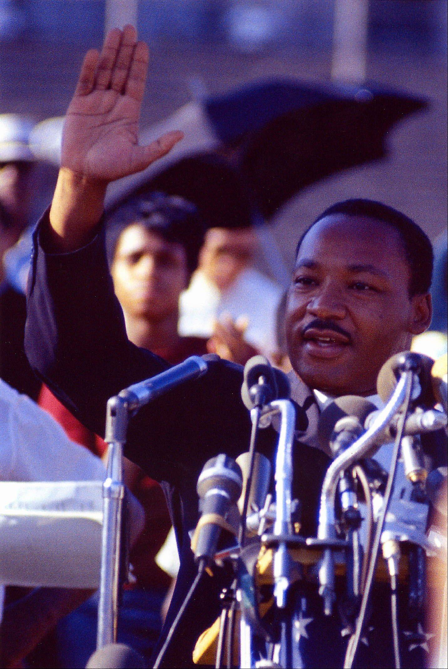 Martin Luther King, Jr., raises his hand to the crowd while speaking at Soldier Field in this undated photo.