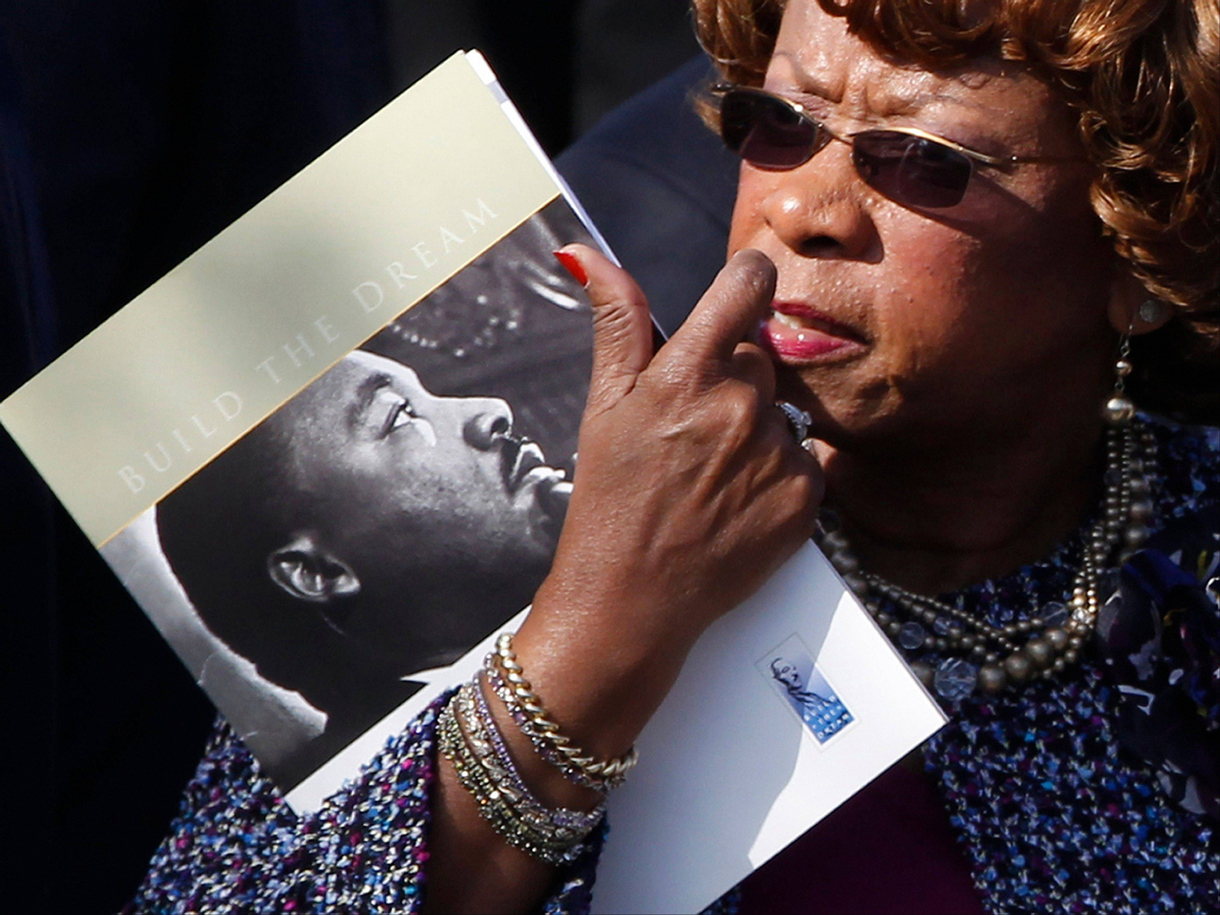 An unidentified guest arrives holding a document bearing the image of Martin Luther King Jr., ahead of President Barack Obama's speech during the dedication of the Martin Luther King Jr. Memorial in Washington, Sunday, Oct. 16, 2011.