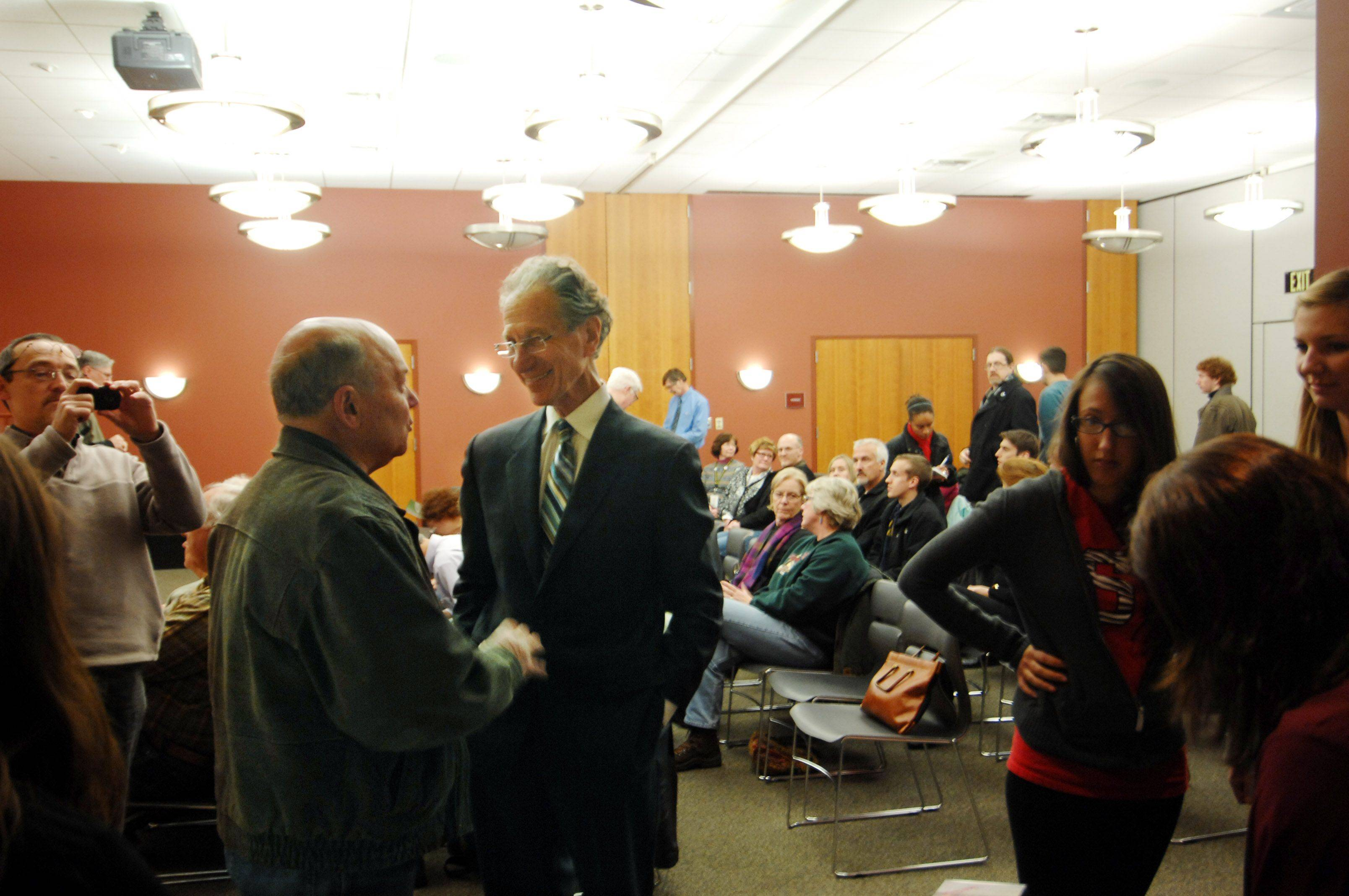 "Elgin Mayor David Kaptain, left, and Harry Wiland, a California-based producer, center, chat before the Midwest premiere of ""Designing Healthy Communities,"" a PBS series that features Elgin, Tuesday at the Gail Borden Public Library in Elgin. About 70 people turned out for the premiere."