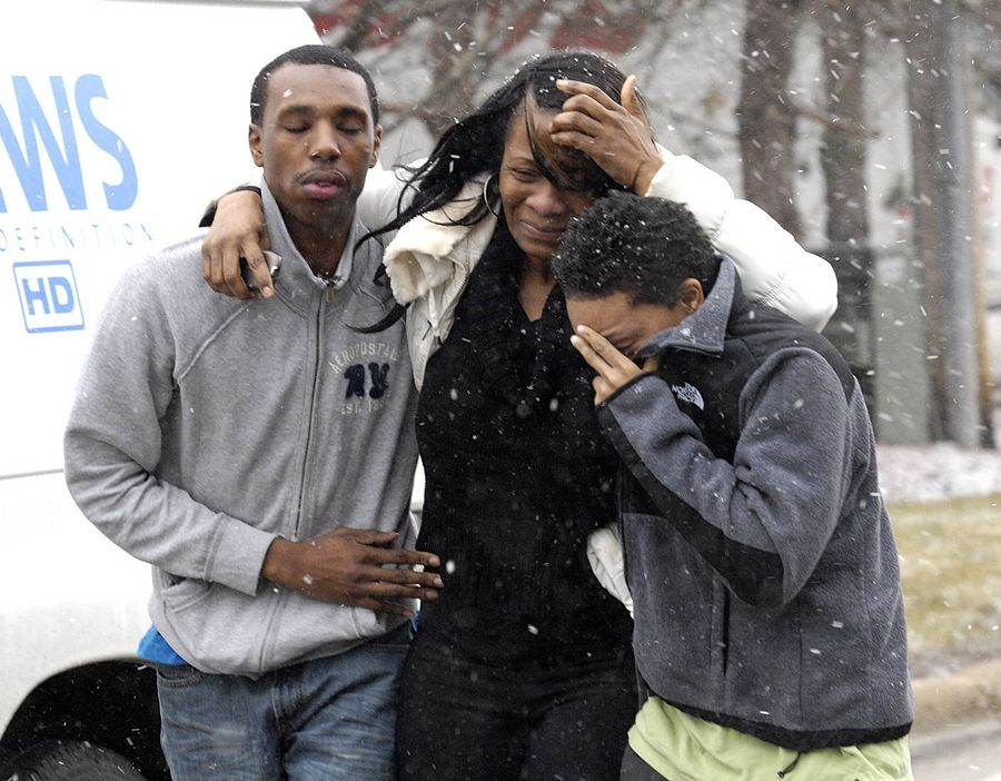Family members of four victims killed Tuesday morning gather at the scene of the shooting and fire on Summit Avenue in an unincorporated area between Oakbrook Terrace and Villa Park.