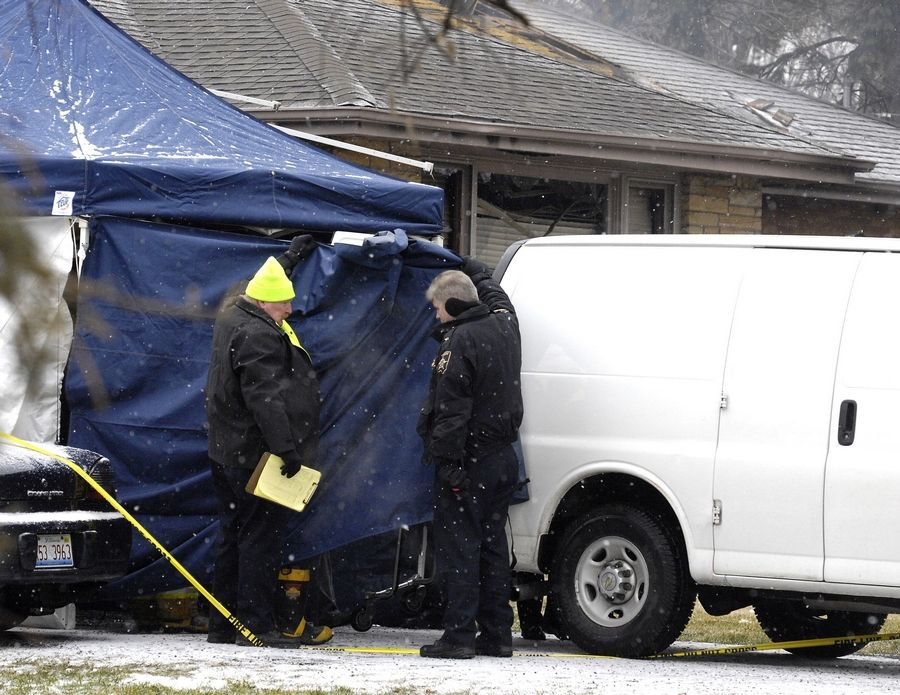 Investigators remove the bodies of the four victims of a shooting and fire Tuesday morning in unincorporated DuPage County between Oakbrook Terrace and Villa Park.