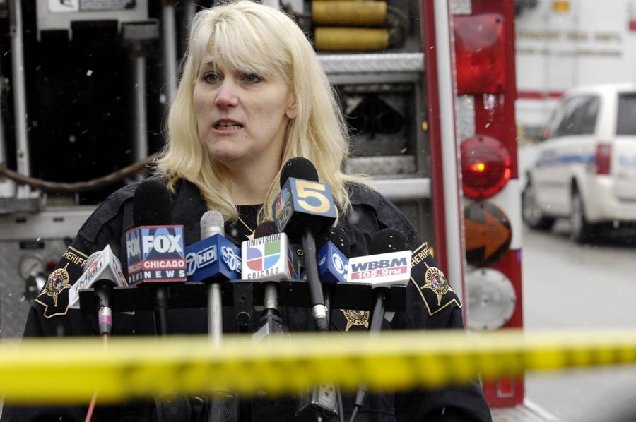 DuPage County sheriff's spokeswoman Dawn Domrose talks to the media as investigators probe the cause of a fire set after the shooting deaths of four people at a home near the intersection of Summit Avenue and Roosevelt Road in unincorporated DuPage County between Oakbrook Terrace and Villa Park.