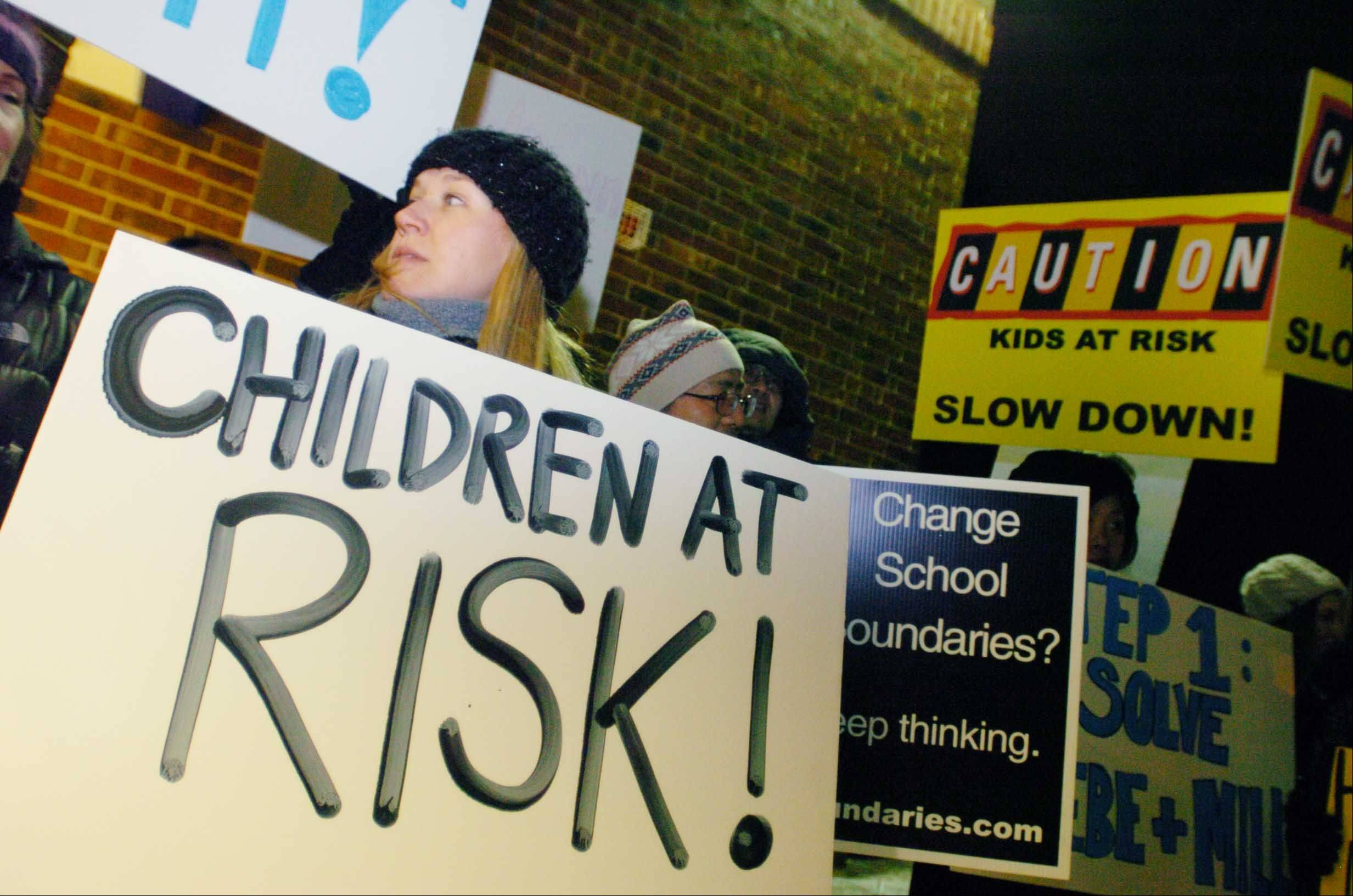 "Jocelyn Harris of Naperville Holds a ""Children At Risk"" sign while attending the protest at Washington Junior High School in Naperville Wednesday. More than 100 protesters took part in the demonstration against plans to redraw some school boundaries in Naperville Unit District 203."
