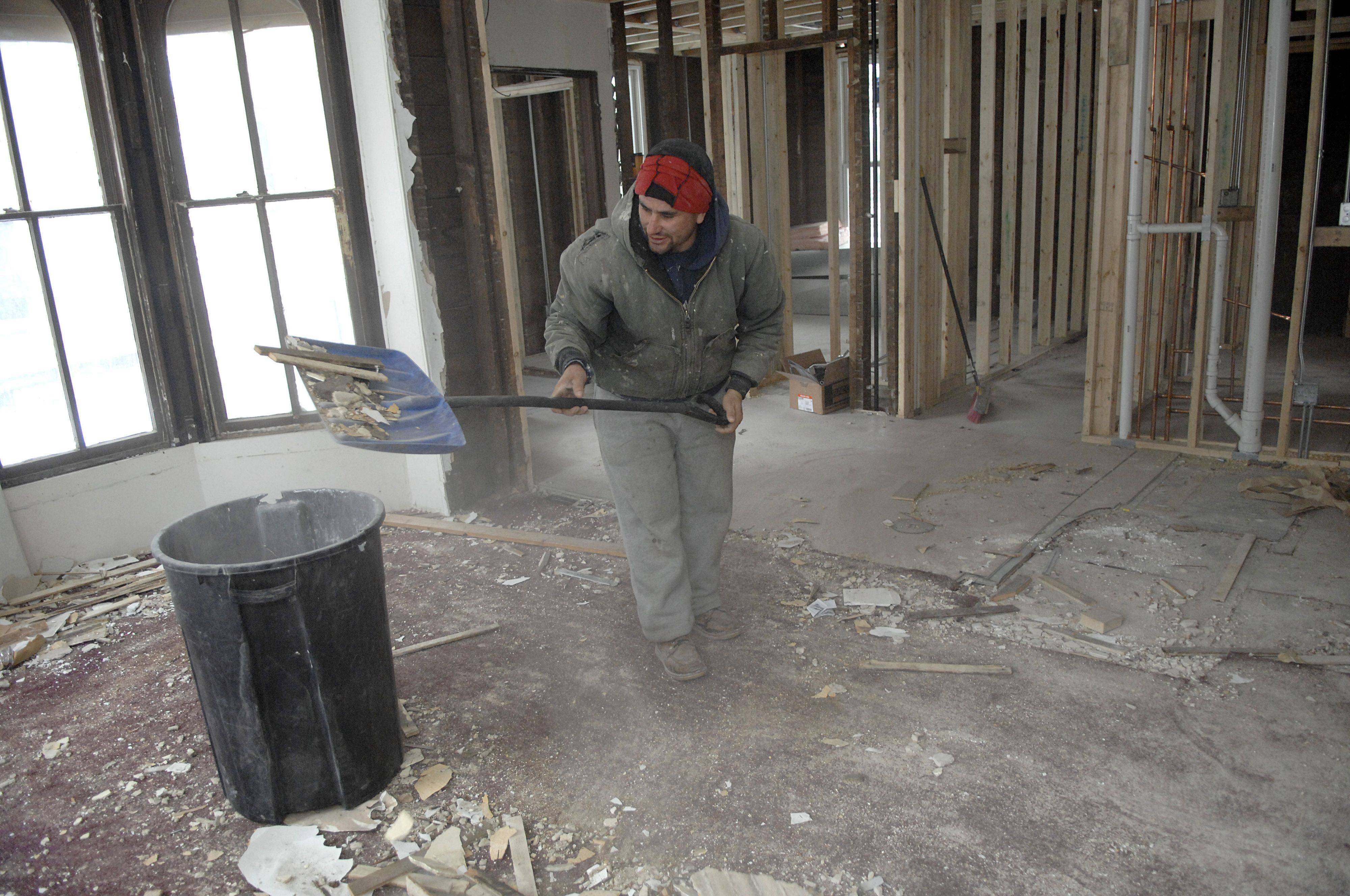 Rogelyo Grimaldo scoops up debris from the rehab at 457 E. Chicago St., another of Elgin's NSP home purchases. The rehabilitation of this home has been completed and the house is now for sale for $215,000.