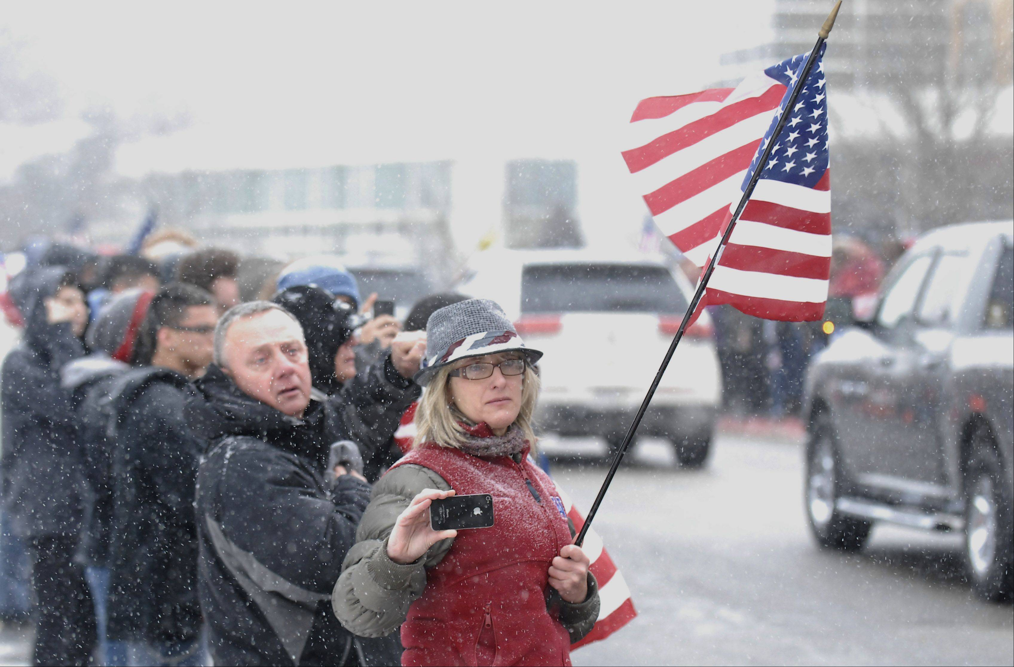 West Aurora teacher Brandi Martin videos the funeral procession of Spc. Christopher A. Patterson as his funeral procession passes his former school on Friday, January 20. Patterson, a 2009 graduate, was killed on January 6.