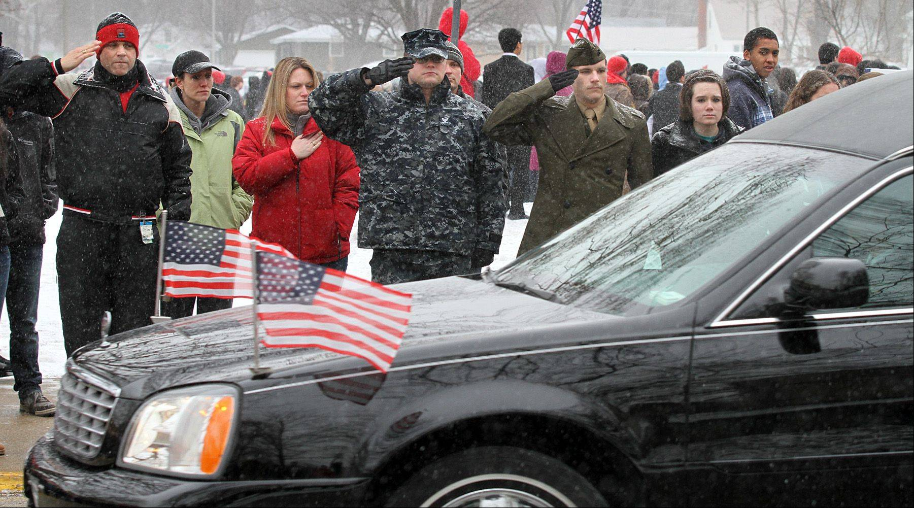 A hearse carrying the body of SPC Christopher Patterson proceeds down Commonwealth Avenue on the campus of West Aurora High School where students, staff and military personnel stood and paid their respects on Friday.