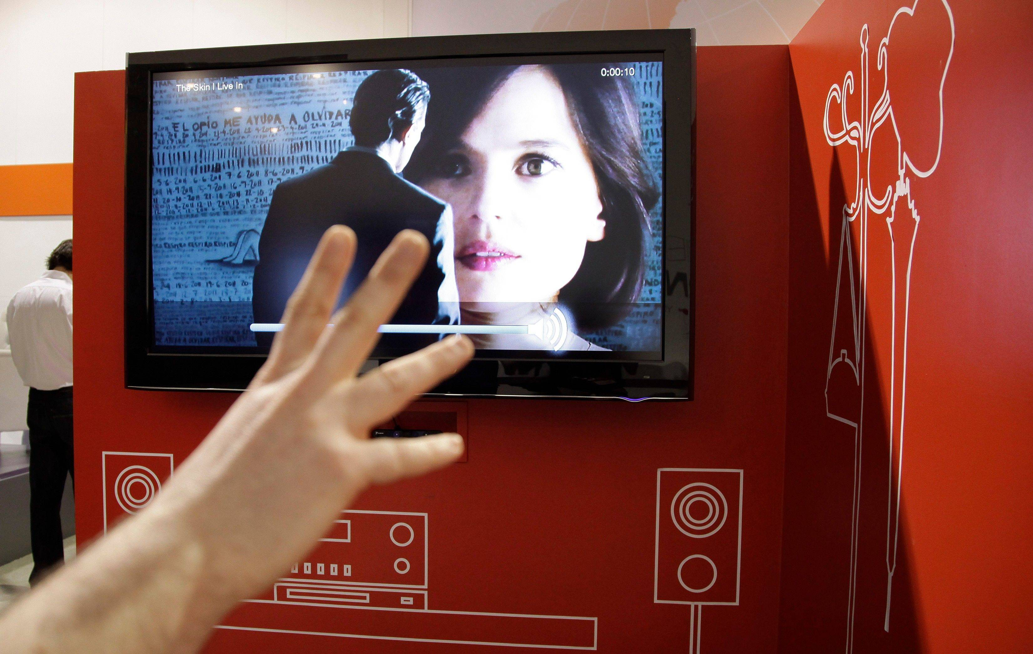 An industry affiliate tries out a Prime Sense depth control camera to change the volume on a television at the 2012 International Consumer Electronics Show in Las Vegas. The technology allows control of electronic devices with body motion.