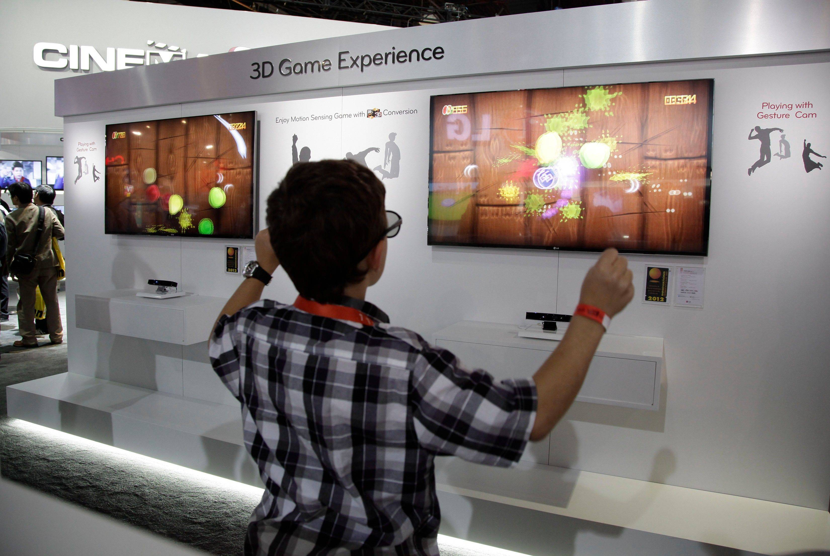 A boy plays with a motion sensing 3-D version of the video game Fruit Ninja at the LG exhibit at the 2012 International CES trade show, in Las Vegas.