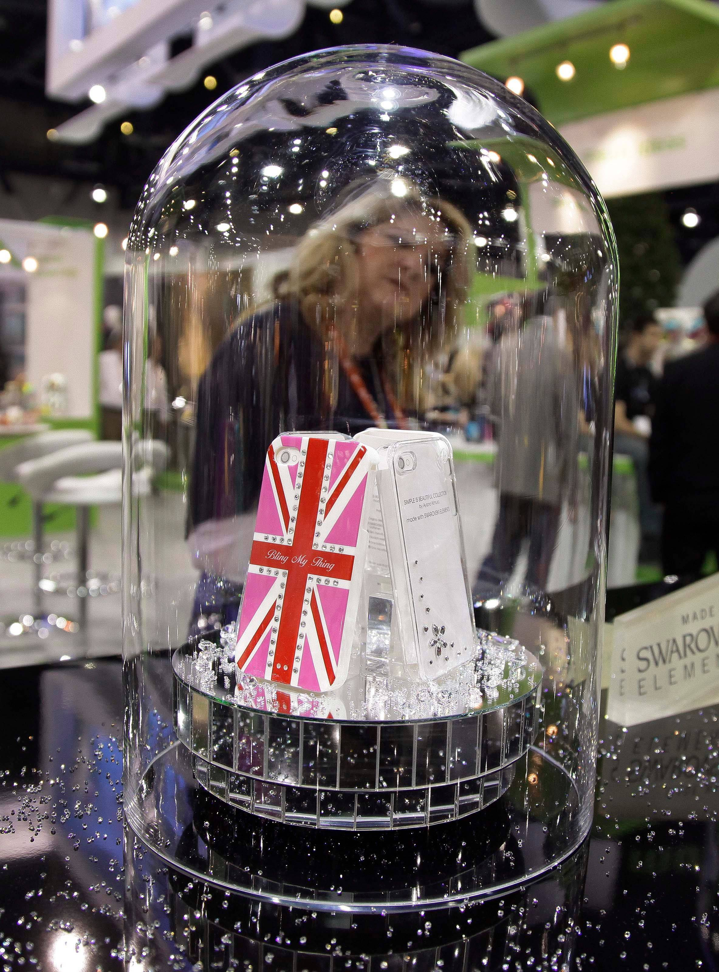 An exhibitor looks over cellphone covers featuring Swarovski crystal trim at the 2012 International Consumer Electronics show.