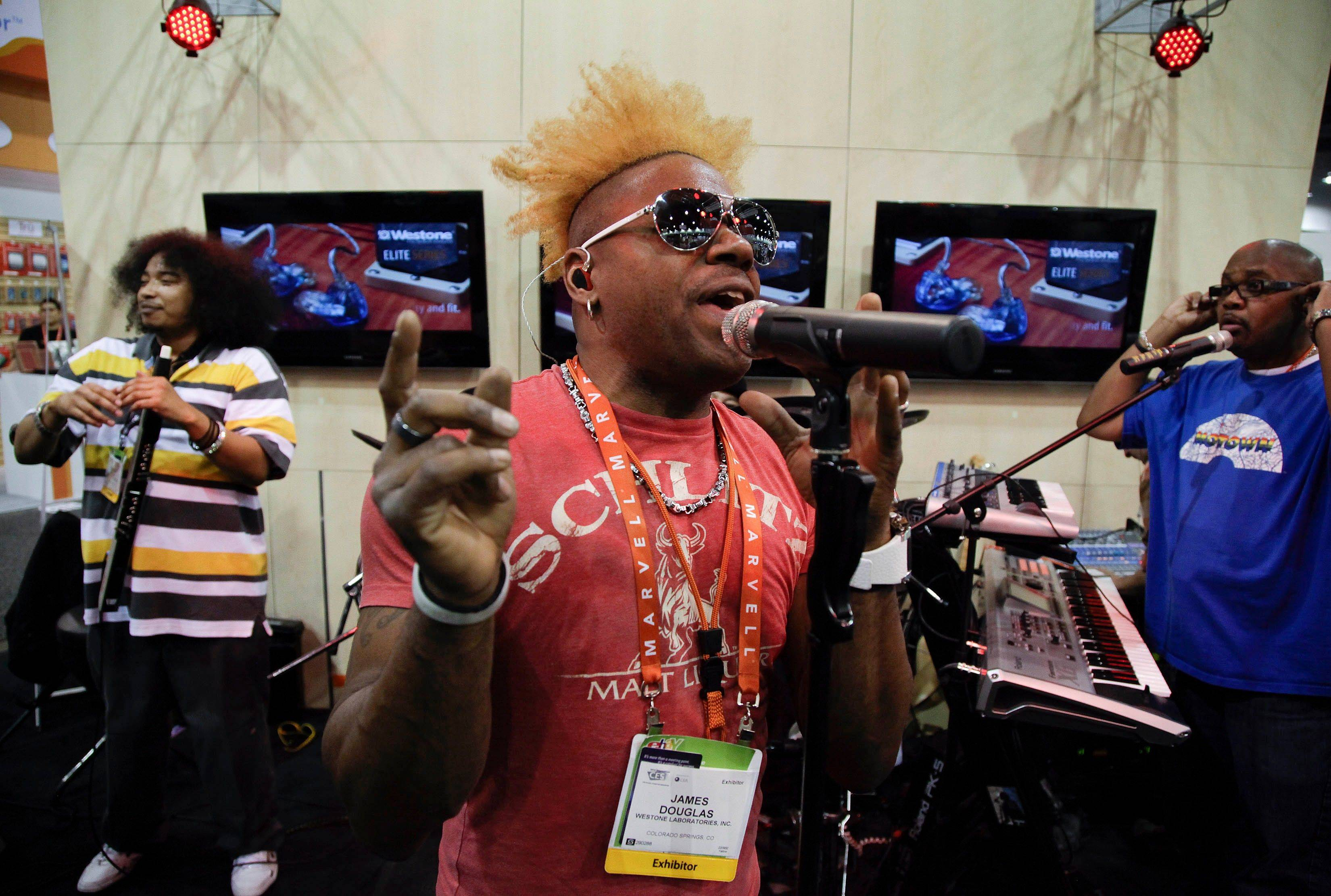 Exhibitor James Douglas sings rap song in the Westone booth to demonstrate the quality of earbuds his company manufactures at the 2012 International Consumer Electronics show.