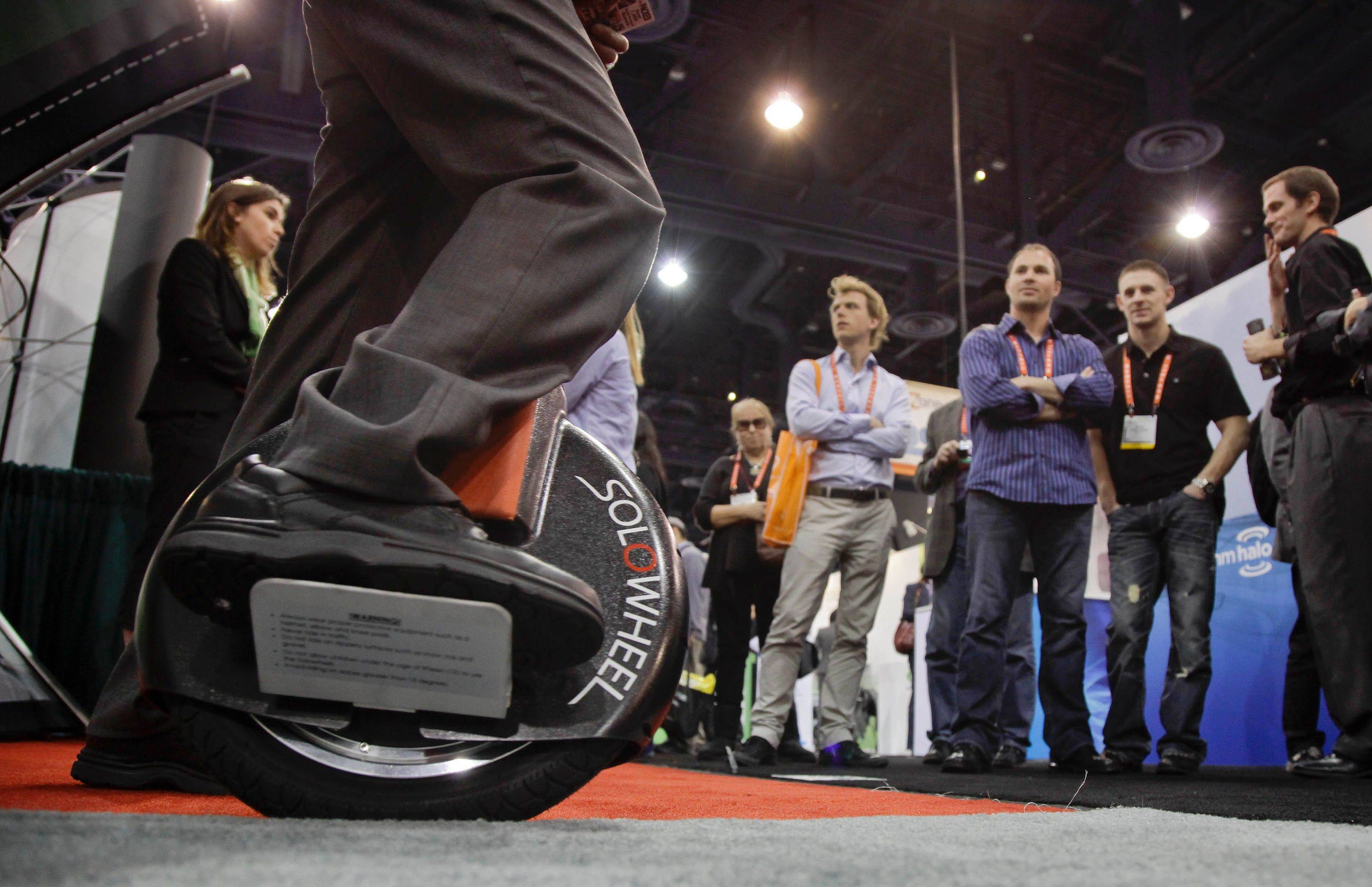 Solowheel at the 2012 International Consumer Electronics Show in Las Vegas. The one-wheeled device, which has no frame or saddle, uses footboards that fold out from the wheel and a gyroscope that helps keep the rider upright.