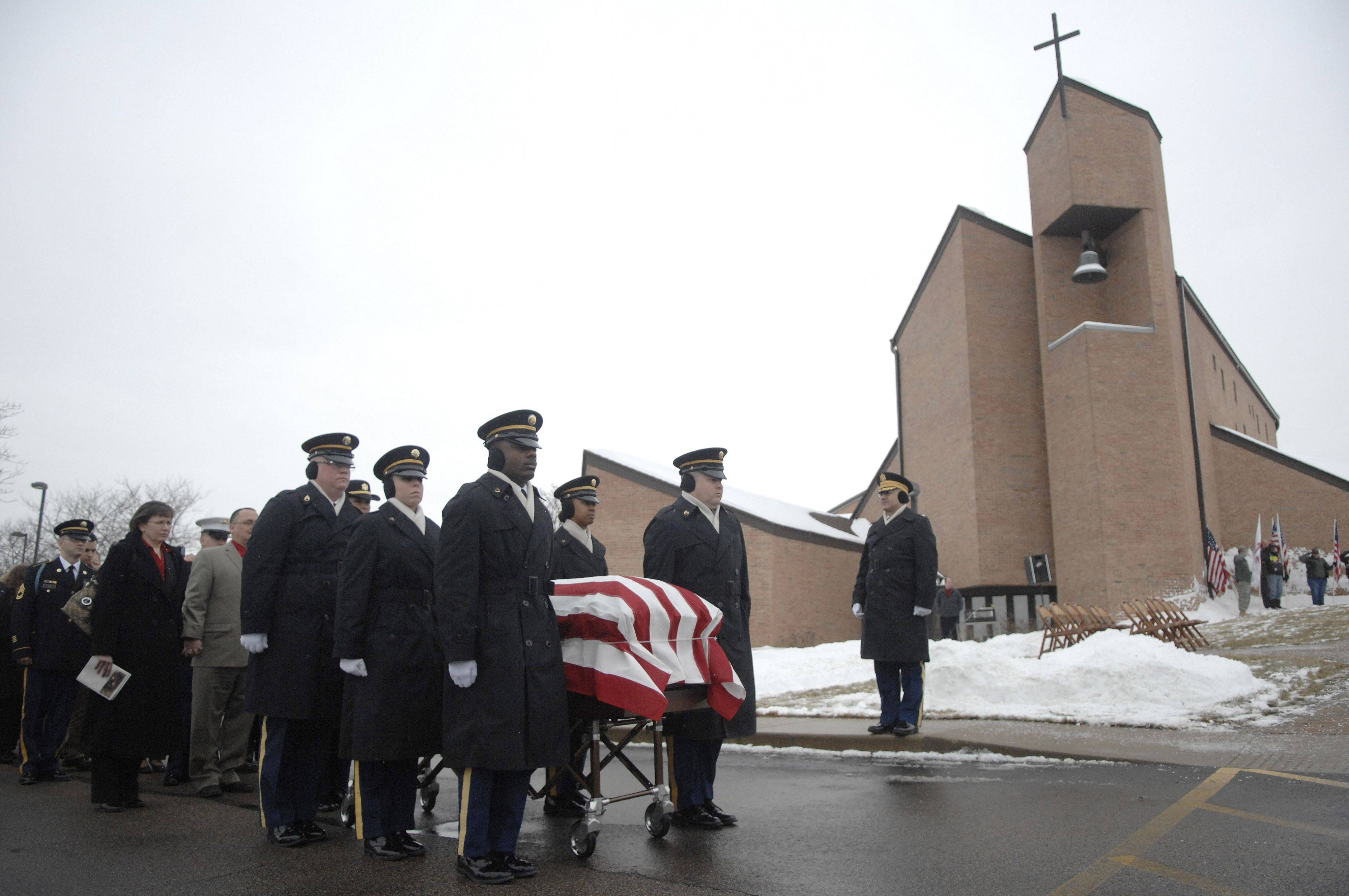 Staff Sergeant Arma Wright, left, and Staff Sergeant Jeffrey Hawley lead the Indiana National Honor Guard Ceremonial Unit in bringing out the casket of Spc. Christopher A. Patterson for full military honors after his funeral at Immanuel Lutheran Church in Batavia on Saturday, January 21.