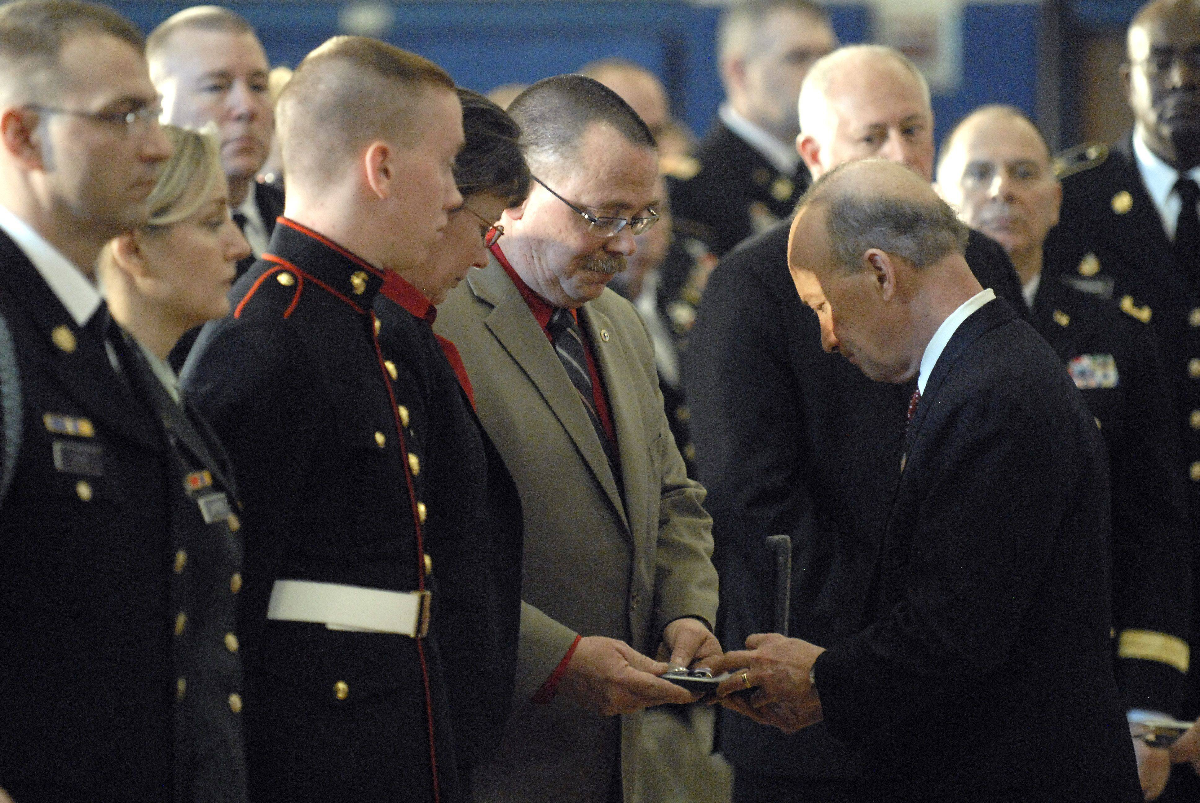 Indiana Governor Mitch Daniels helps in the presentation of medals to Bob and Mary Patterson, parents of Spc. Christopher A. Patterson at his funeral in Batavia. Patterson, a member of the 713th Engineer Company of the Indiana National Guard, was awarded the Purple Heart and Bronze Star.