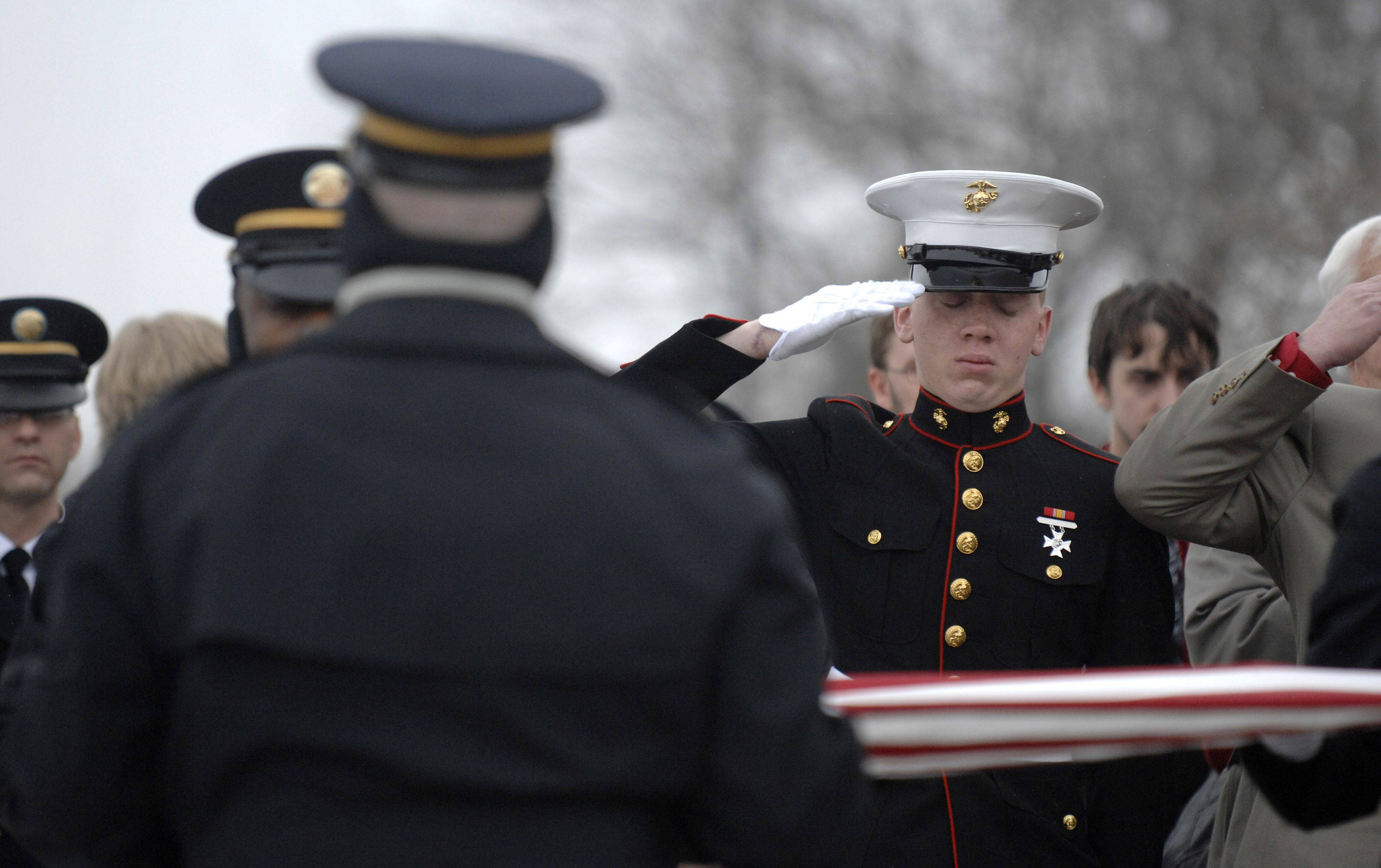Carl Patterson, brother of Spc. Christopher A. Patterson, salutes and closes his eyes while Taps is played during full military honors outside Immanuel Lutheran Church in Batavia on Saturday, January 21.
