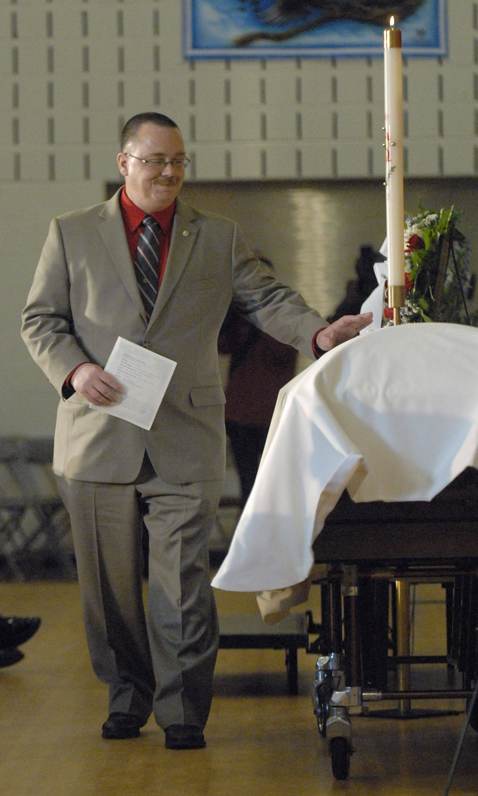 Bob Patterson, father of Spc. Christopher A. Patterson, pats his son's coffin after sharing a few words at the close of his funeral service at Immanuel Lutheran Church in Batavia on Saturday, January 21.