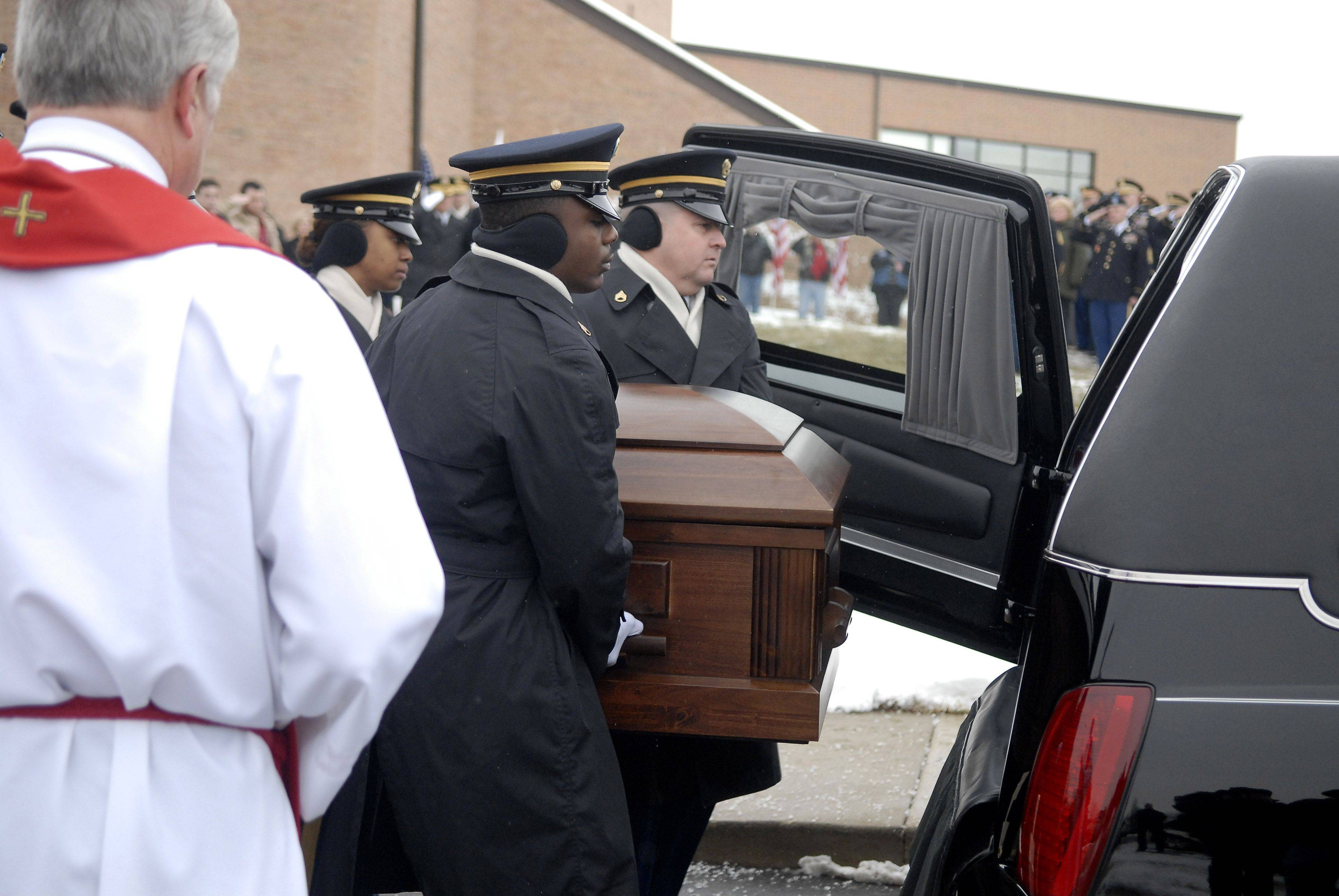 Staff Sergeant Arma Wright, left, and Staff Sergeant Jeffrey Hawley lead the Indiana National Honor Guard Ceremonial Unit in placing the casket of Spc. Christopher A. Patterson into the hearse after his funeral and full military honors at Immanuel Lutheran Church in Batavia on Saturday, January 21.