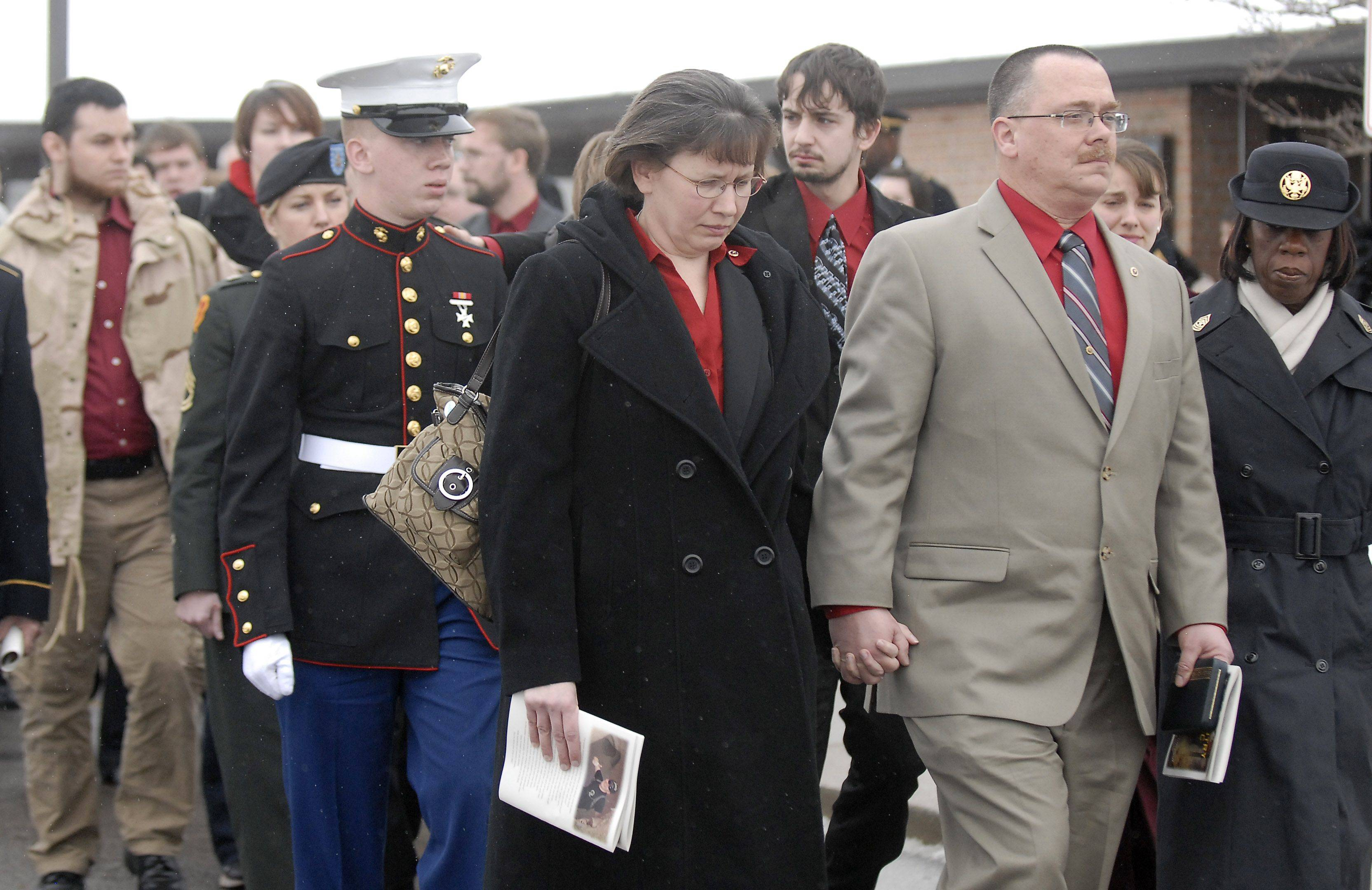 Mary and Bob Patterson walk behind the casket of their son, Spc. Christopher A. Patterson, along with another son, Carl, as they head outside for full military honors at his funeral. Patterson was a member of the 713th Engineer Company of the Indiana National Guard.