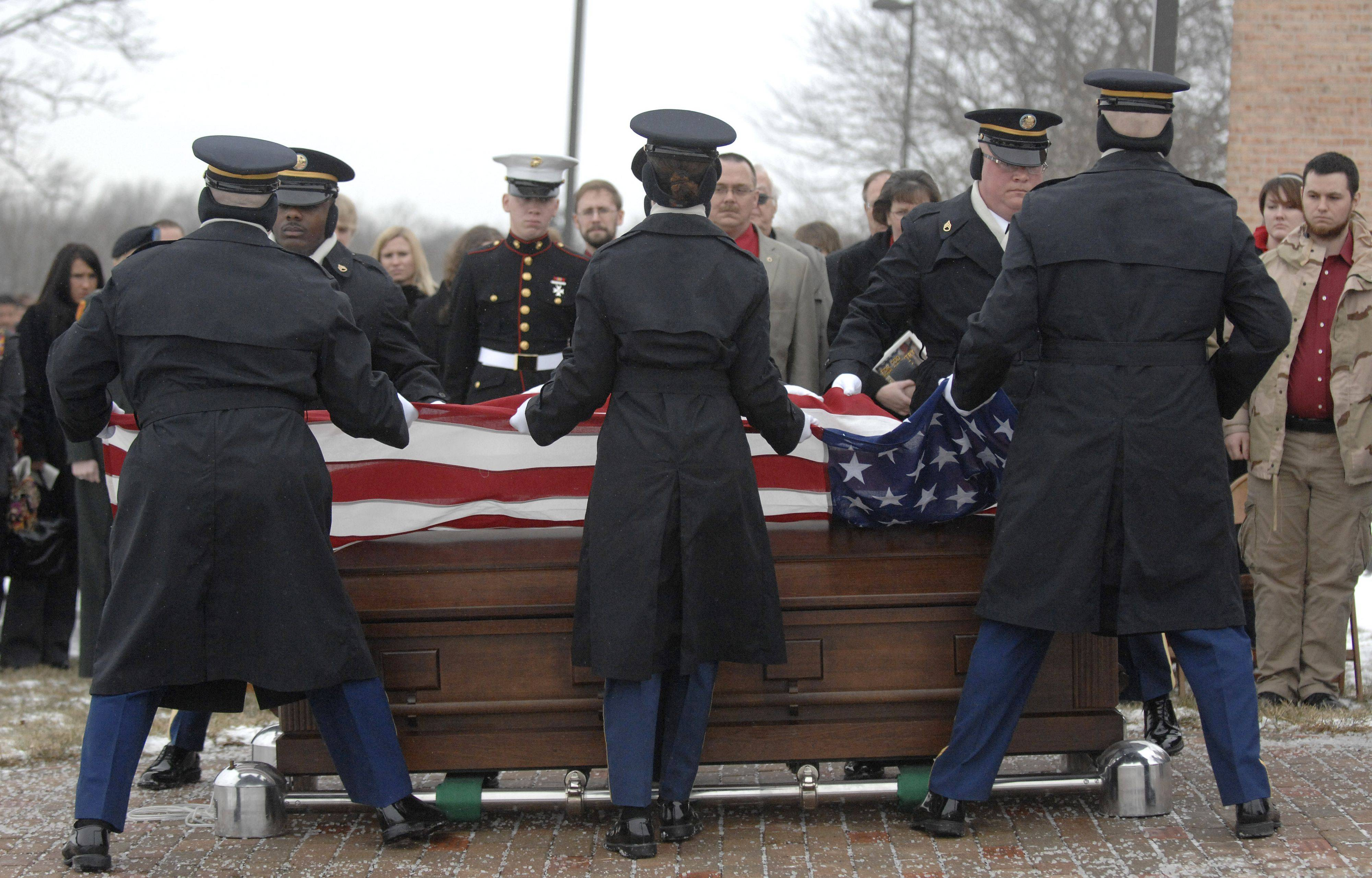 The Ceremonial Unit of the Indiana National Honor Guard fold the flag on Spc. Christopher A. Patterson's casket to be given to his family after his funeral and full military honors at Immanuel Lutheran Church in Batavia on Saturday, January 21.