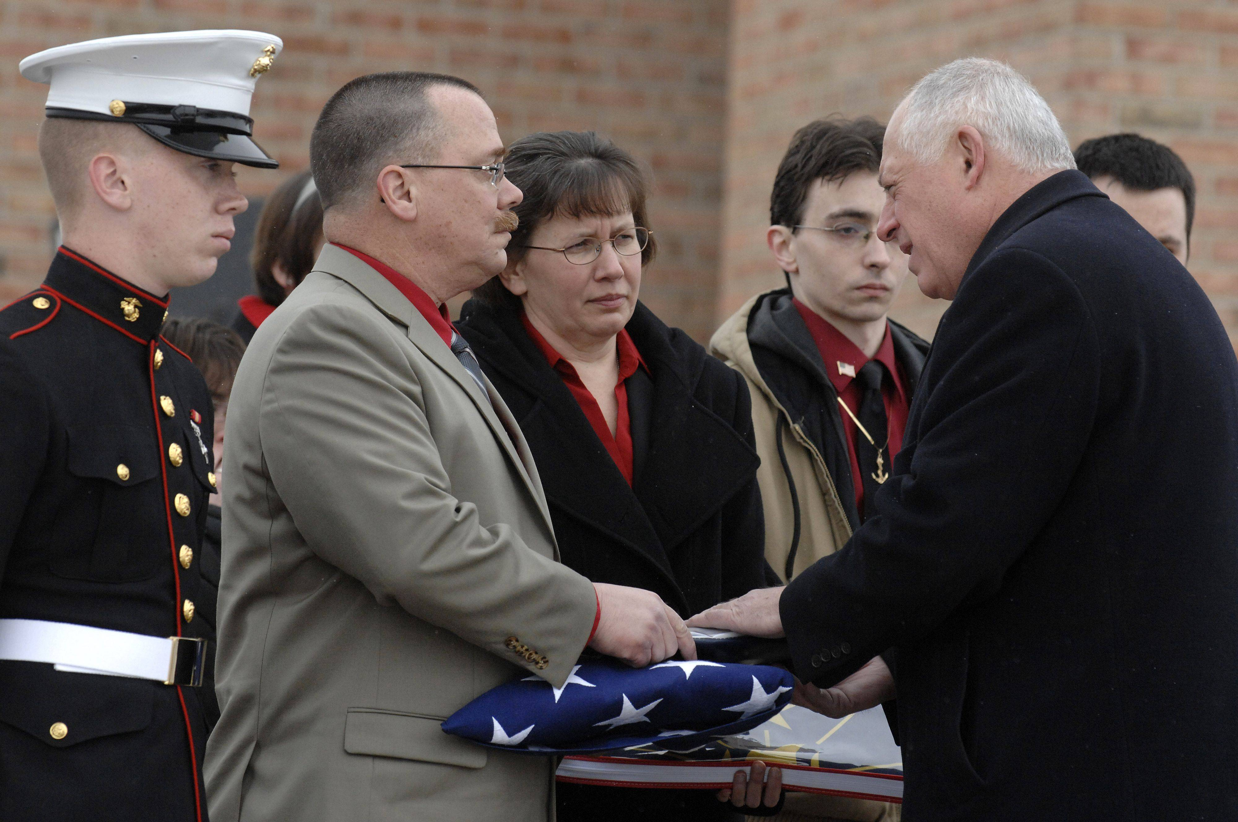 Illinois Governor Pat Quinn presents the Illinois state flag to Bob and Mary Patterson of North Aurora at the funeral of their son, Spc. Christopher A. Patterson. Sons Carl, left, Thomas, right and Sean (behind Quinn) stand by.
