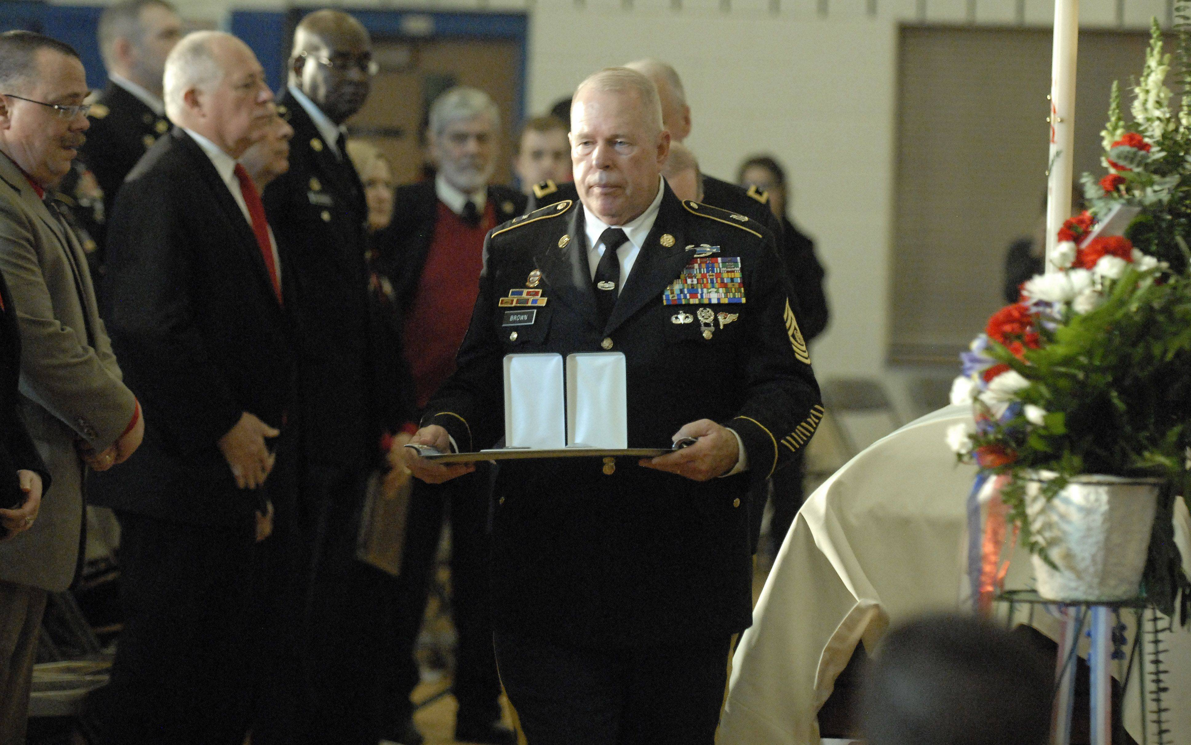 A Purple Heart and Bronze Star are brought to be presented to the parents of Spc. Christopher A. Patterson, a member of the 713th Engineer Company of the Indiana National Guard, at his funeral in Batavia on Saturday, January 21.
