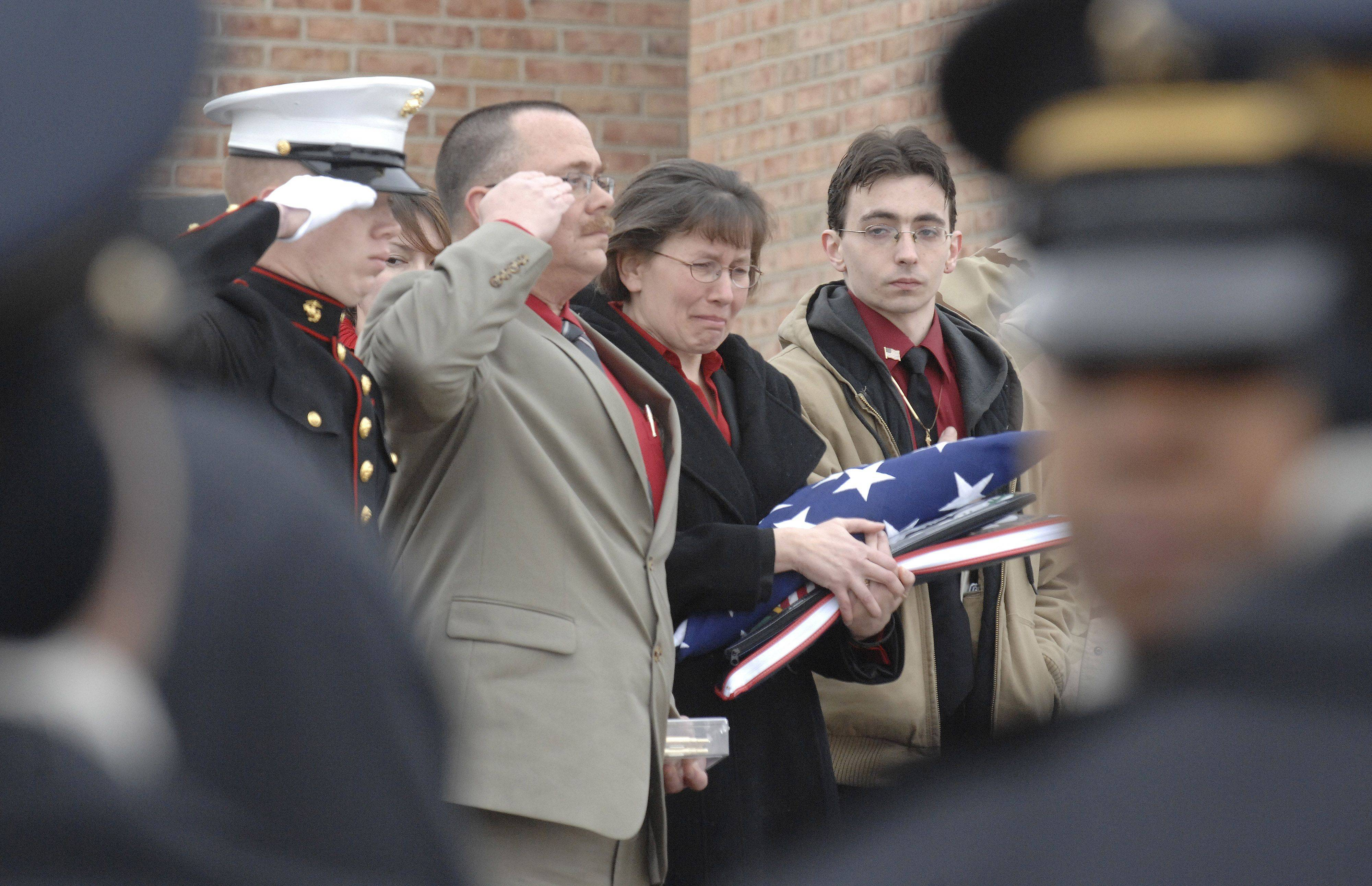 Mary Patterson breaks down while the casket of her son, Spc. Christopher A. Patterson, is placed into the hearse at the close of his funeral and full military honors in Batavia on Saturday, January 21. She is flanked by son, Carl, far left, husband Bob, and son Thomas, right.