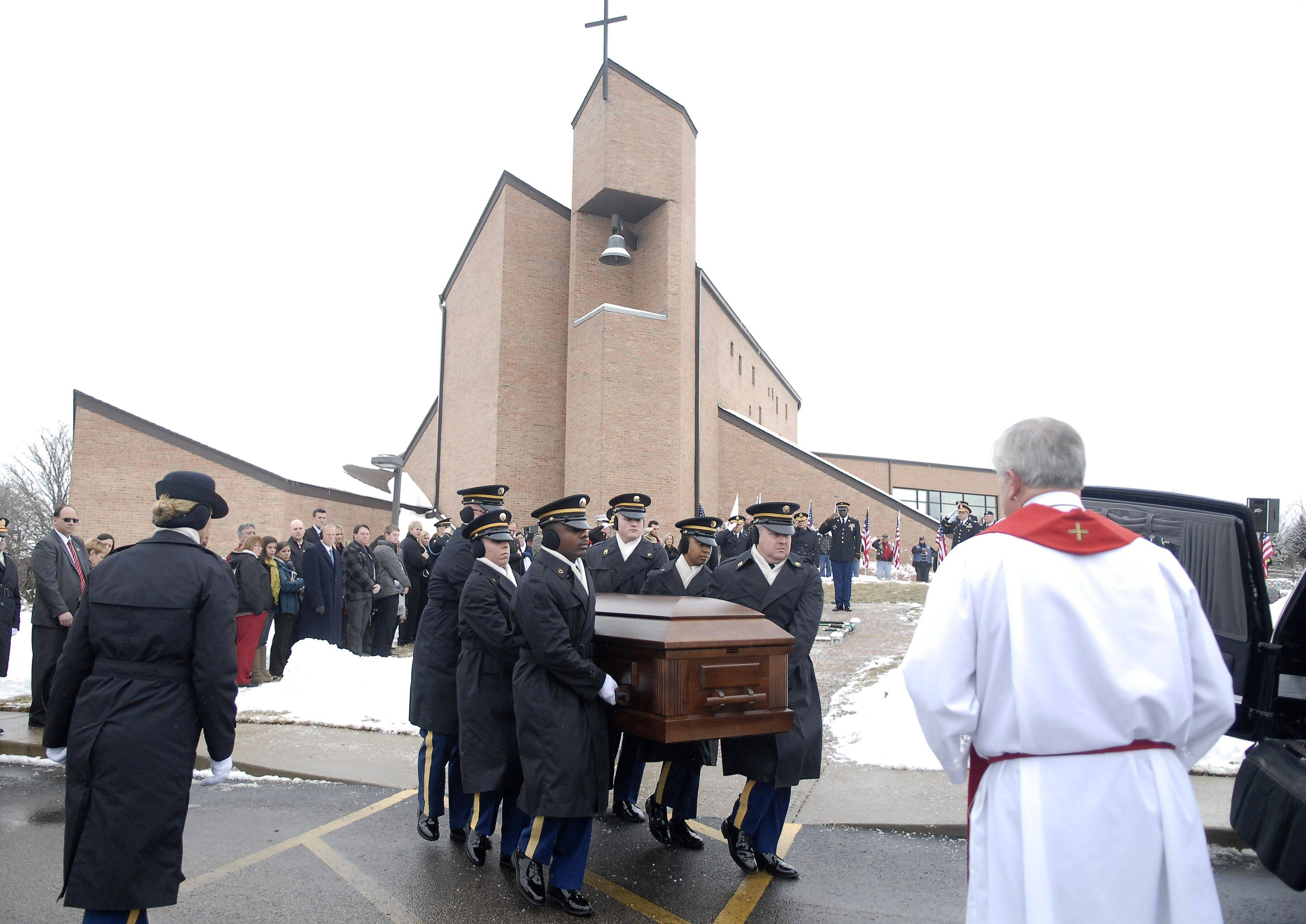 Staff sergeants Arma Wright, left, and Jeffrey Hawley lead the Indiana National Honor Guard Ceremonial Unit in placing the casket of Spc. Christopher Patterson into the hearse after his funeral with full military honors at Immanuel Lutheran Church in Batavia Saturday.