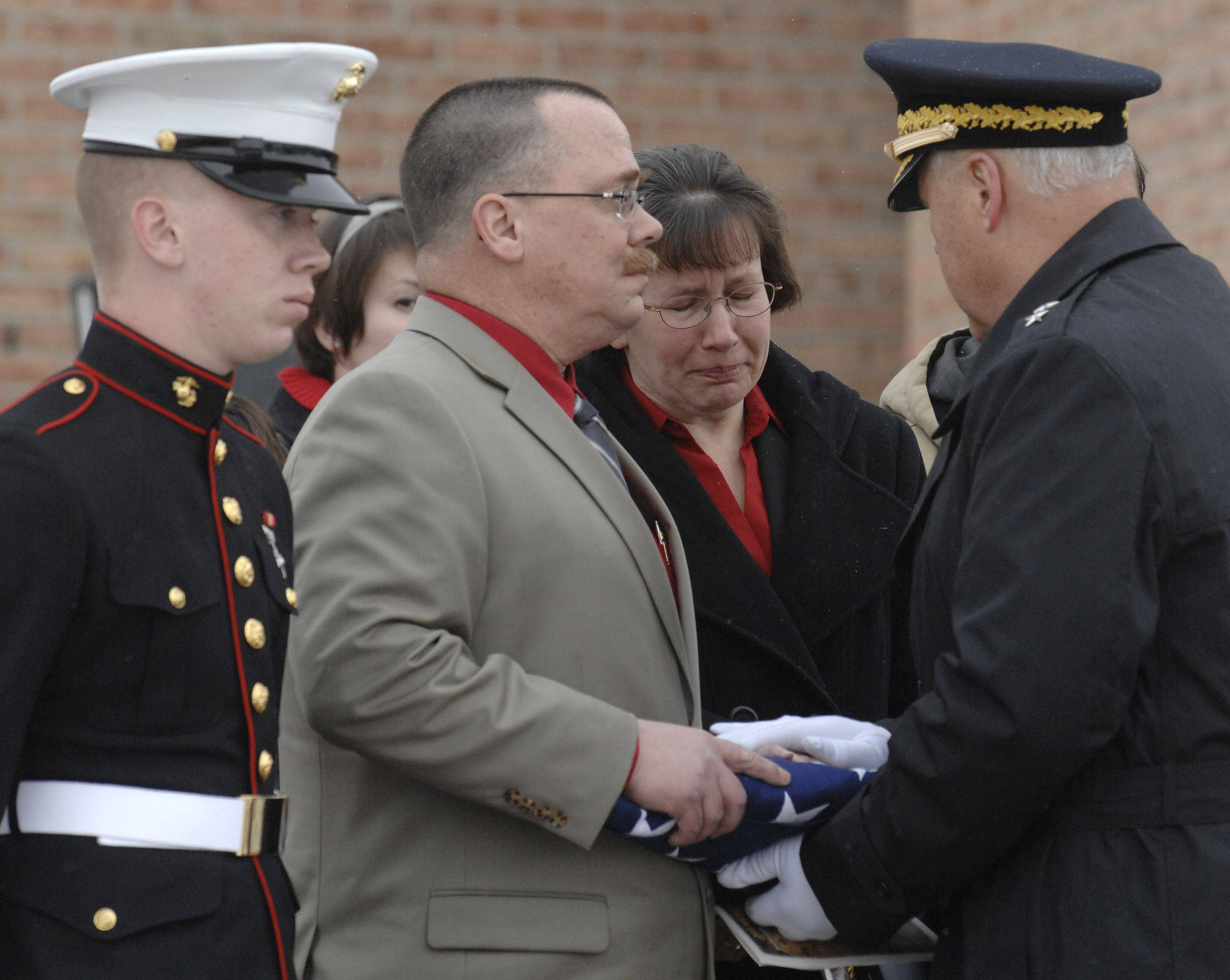 Major General R. Martin Umbarger of the Indiana National Guard presents the flag, which draped the casket of Spc. Christopher Patterson, to his parents Bob and Mary Patterson. The Pattersons' son Carl is at left.