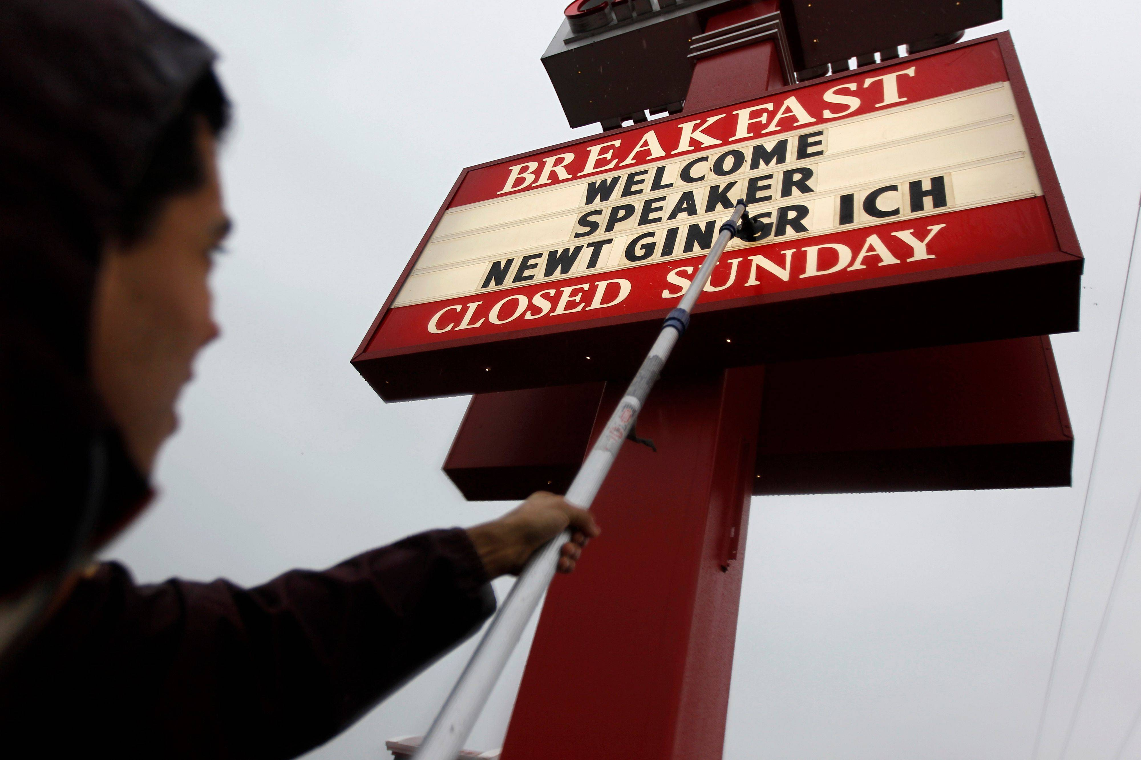 Oscar Lopez mounts letters onto a sign Saturday before a campaign event for Republican presidential candidate, former House Speaker Newt Gingrich at a Chick-Fil-A in Anderson, S.C., on South Carolina's Republican primary election day.