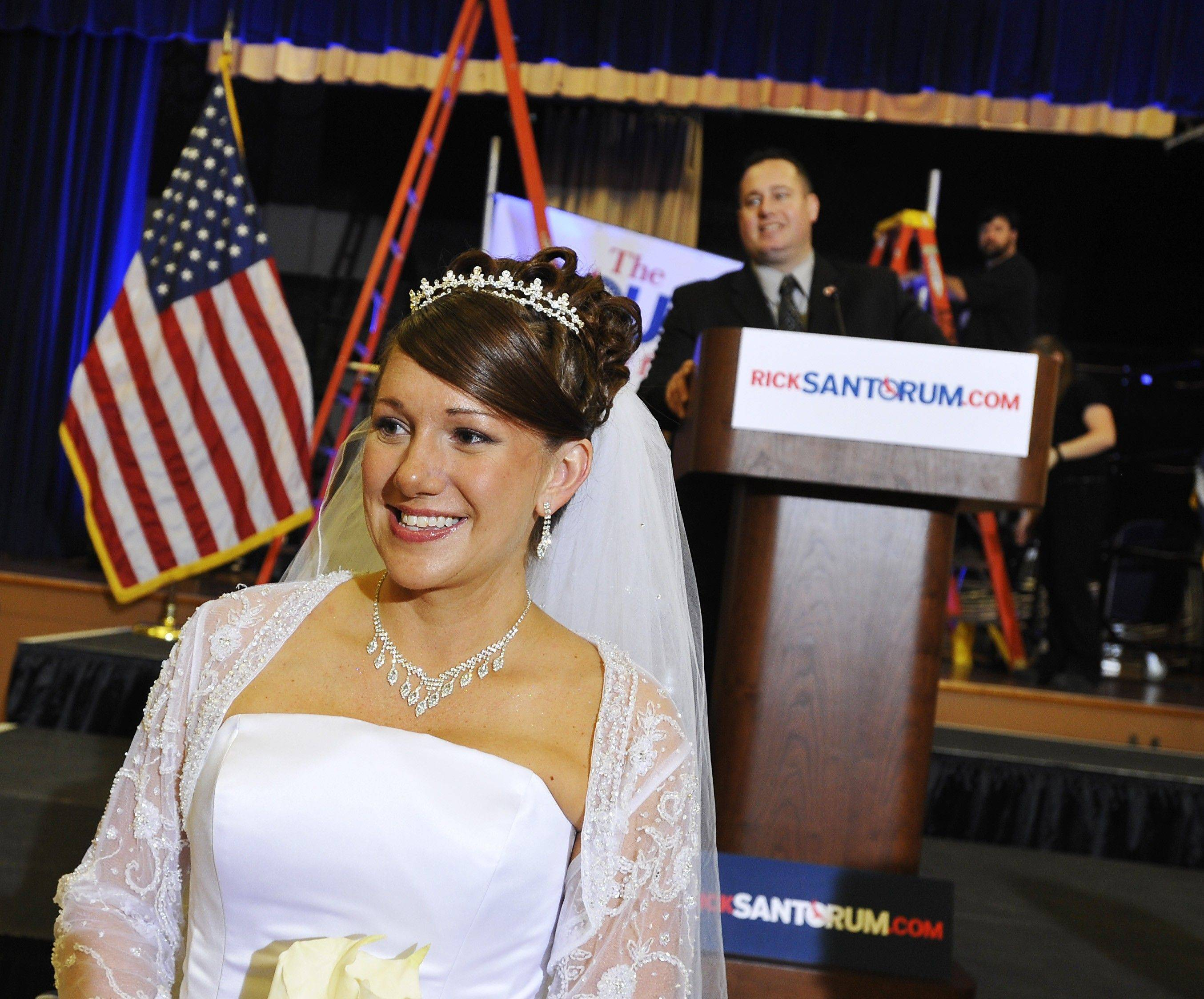 Sarah Heath, left, poses Saturday for a wedding photographer on her wedding day as Rick Santorum campaign volunteer Mike Rendino looks on at the podium before a primary elections party at the Citadel in Charleston, S.C.