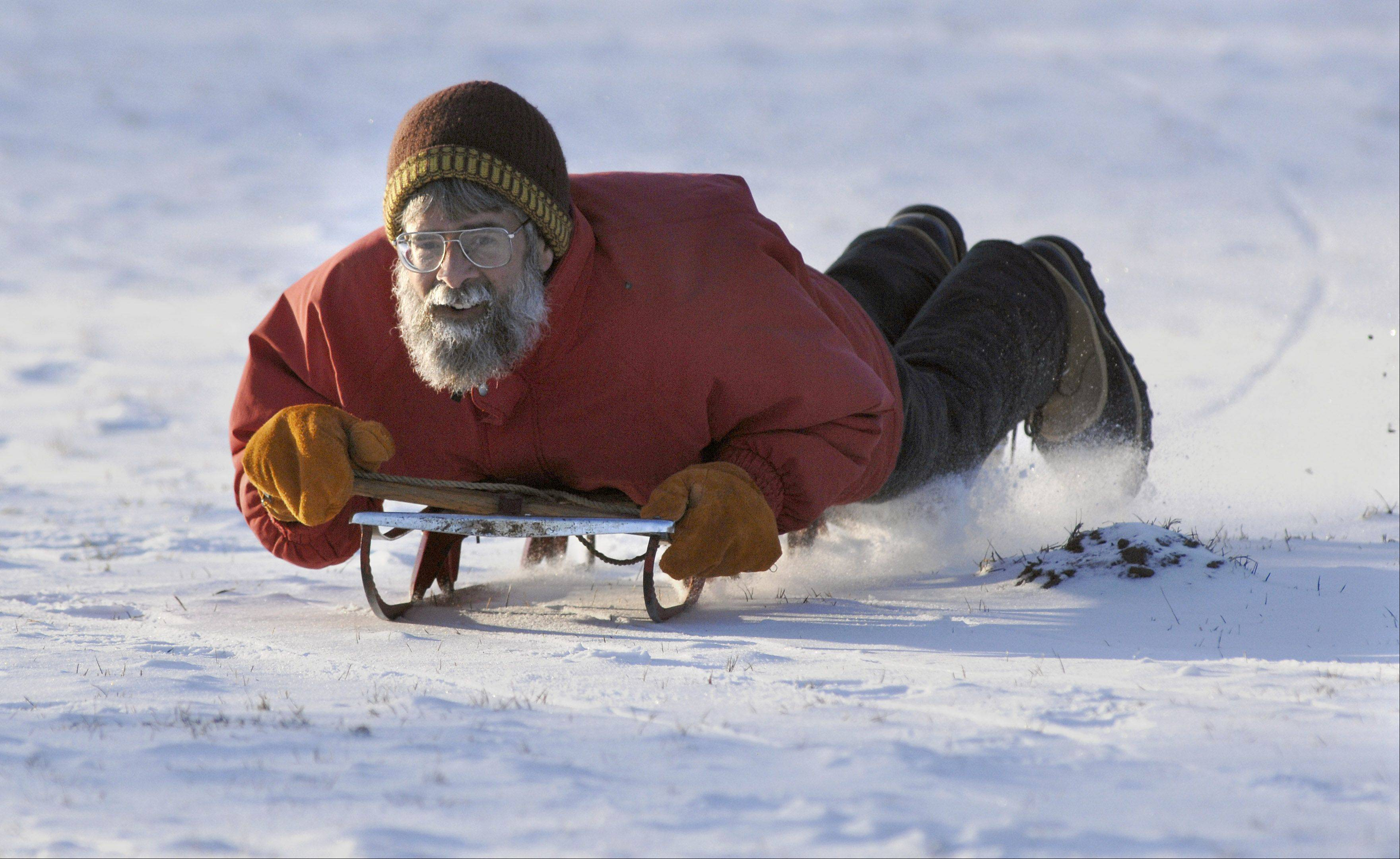 Don Hennen of Geneva zips down the hill at Johnson's Mound in Elburn on Thursday afternoon, January 19. He's had the toboggan since he was a kid, modifying and fixing it up as needed.